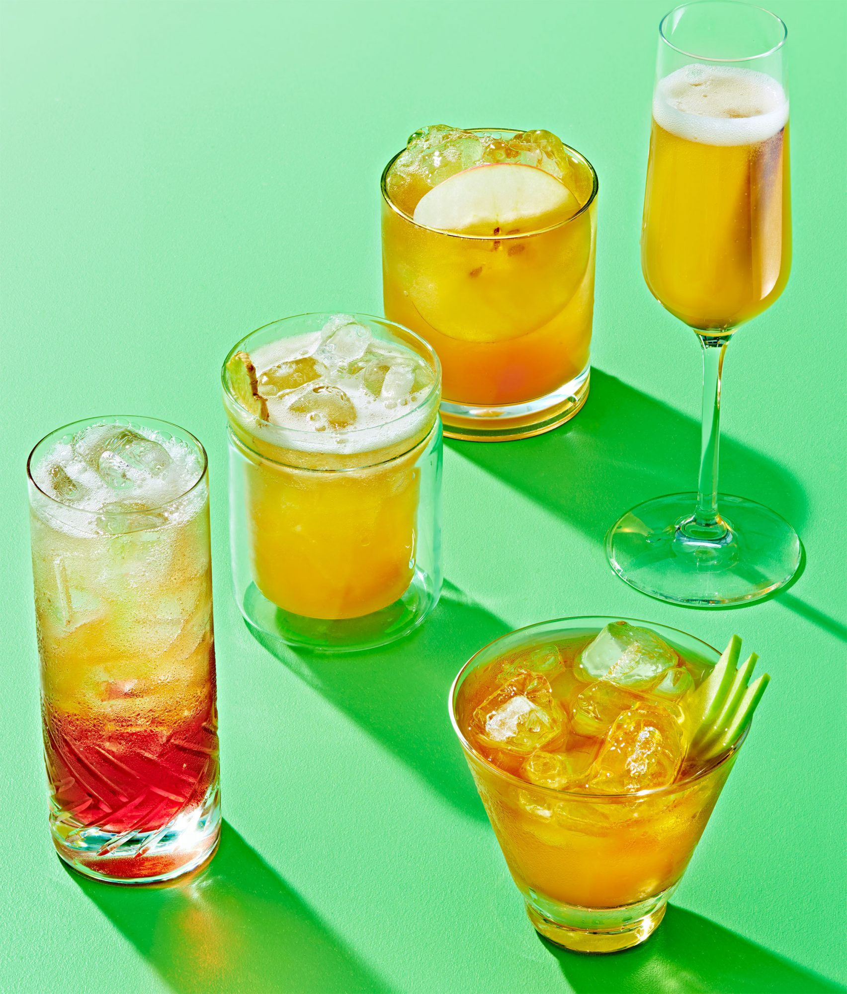 five glasses filled with drinks on a bright green surface
