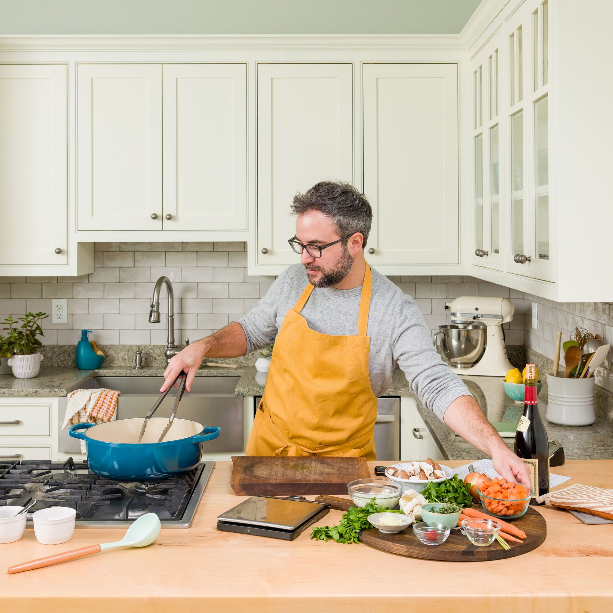 man with beard and yellow apron cooking in a bright white kitchen