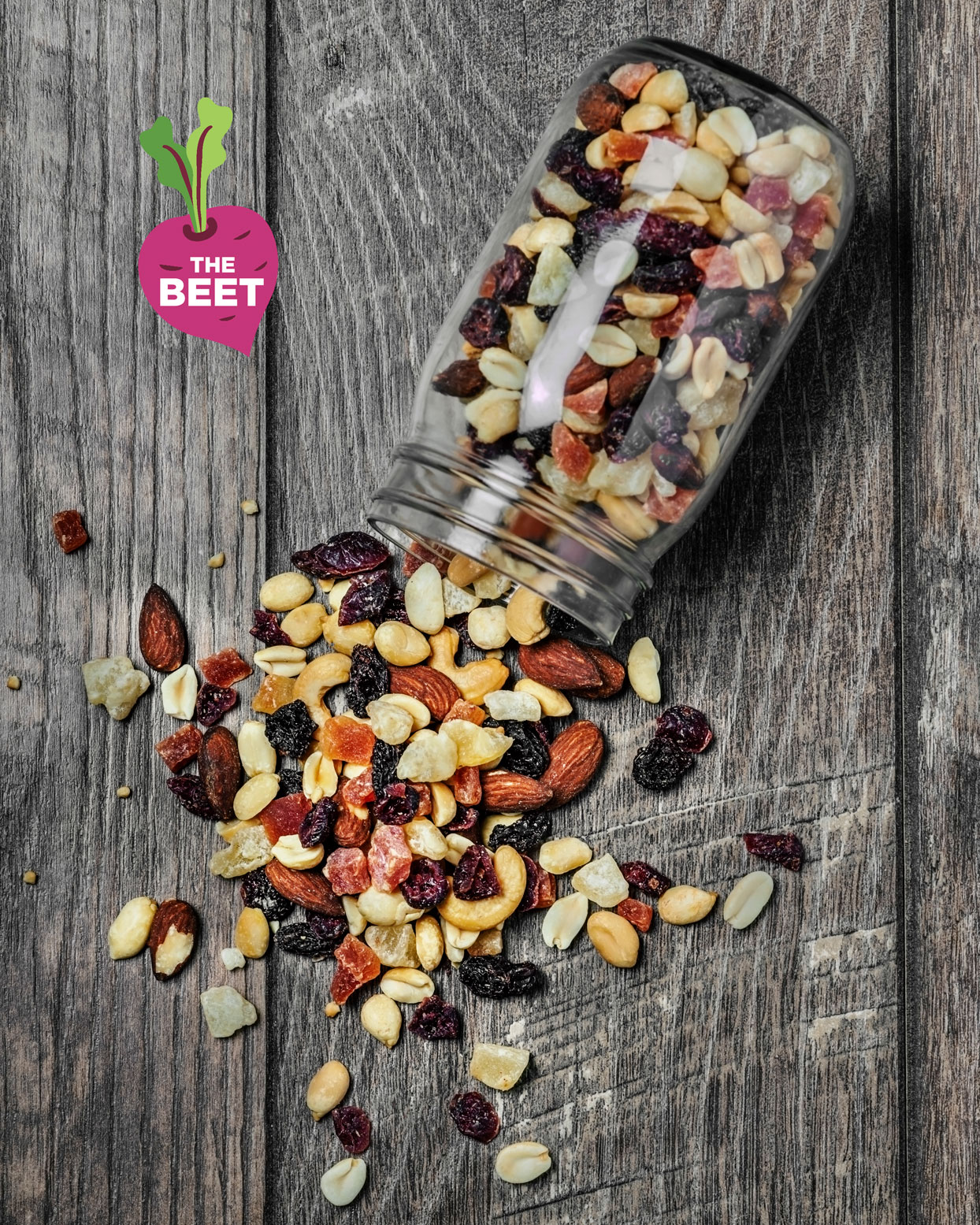 trail mix in mason jar on wooden background with the beet logo on top