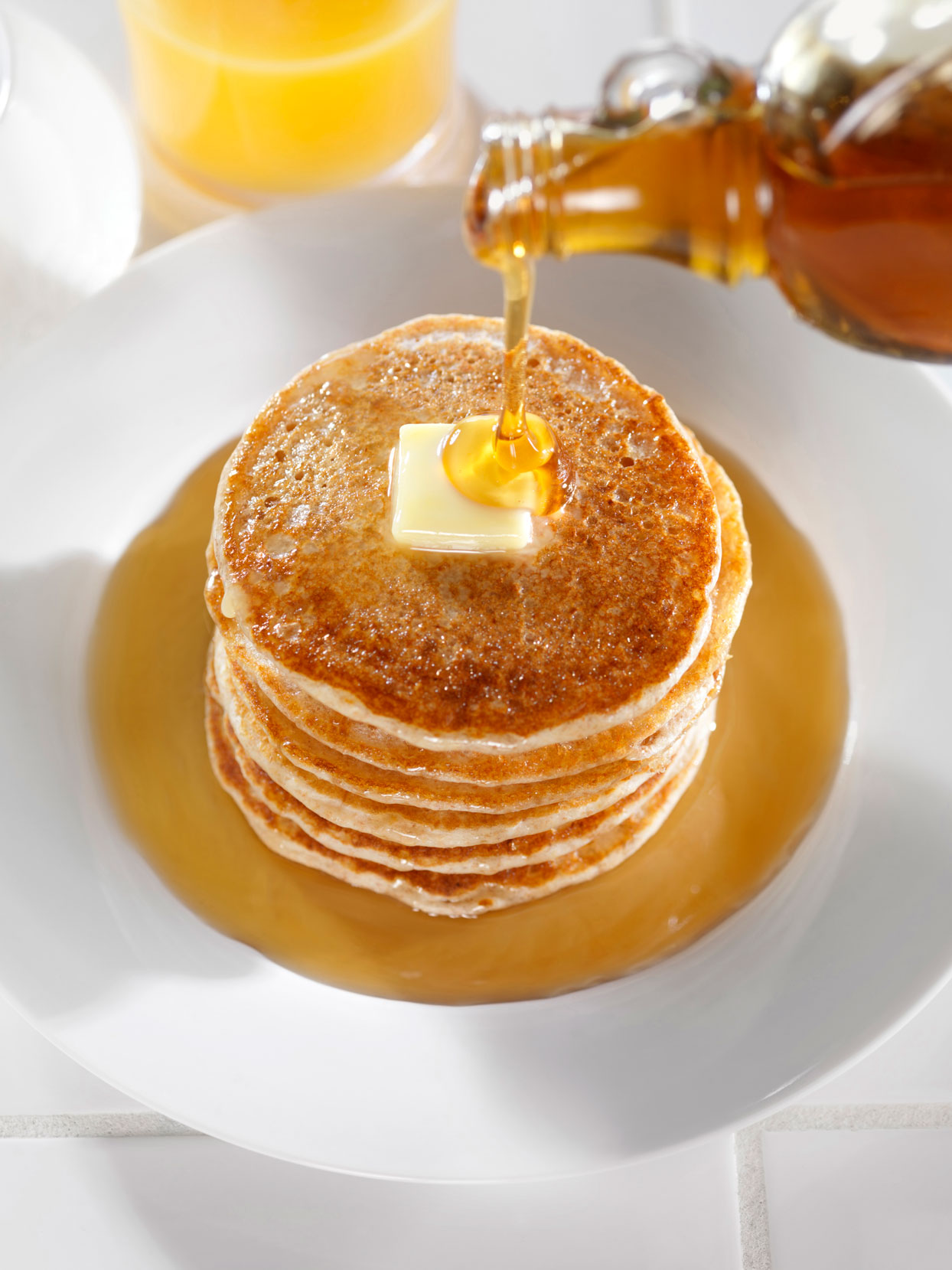 stack of pancakes with butter and maple syrup on a white plate