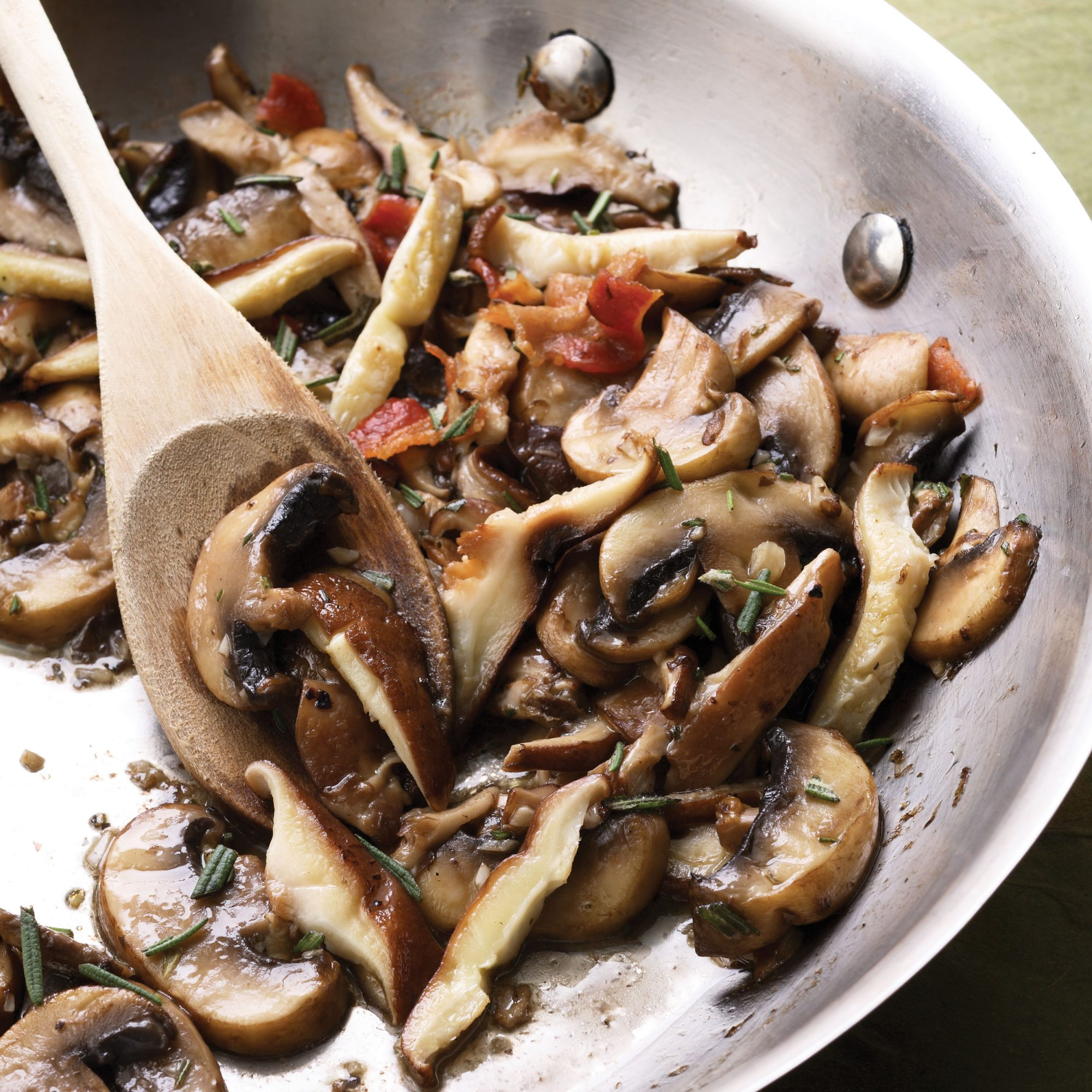 sauteed mushrooms in a stainless steel pan with a wooden spoon