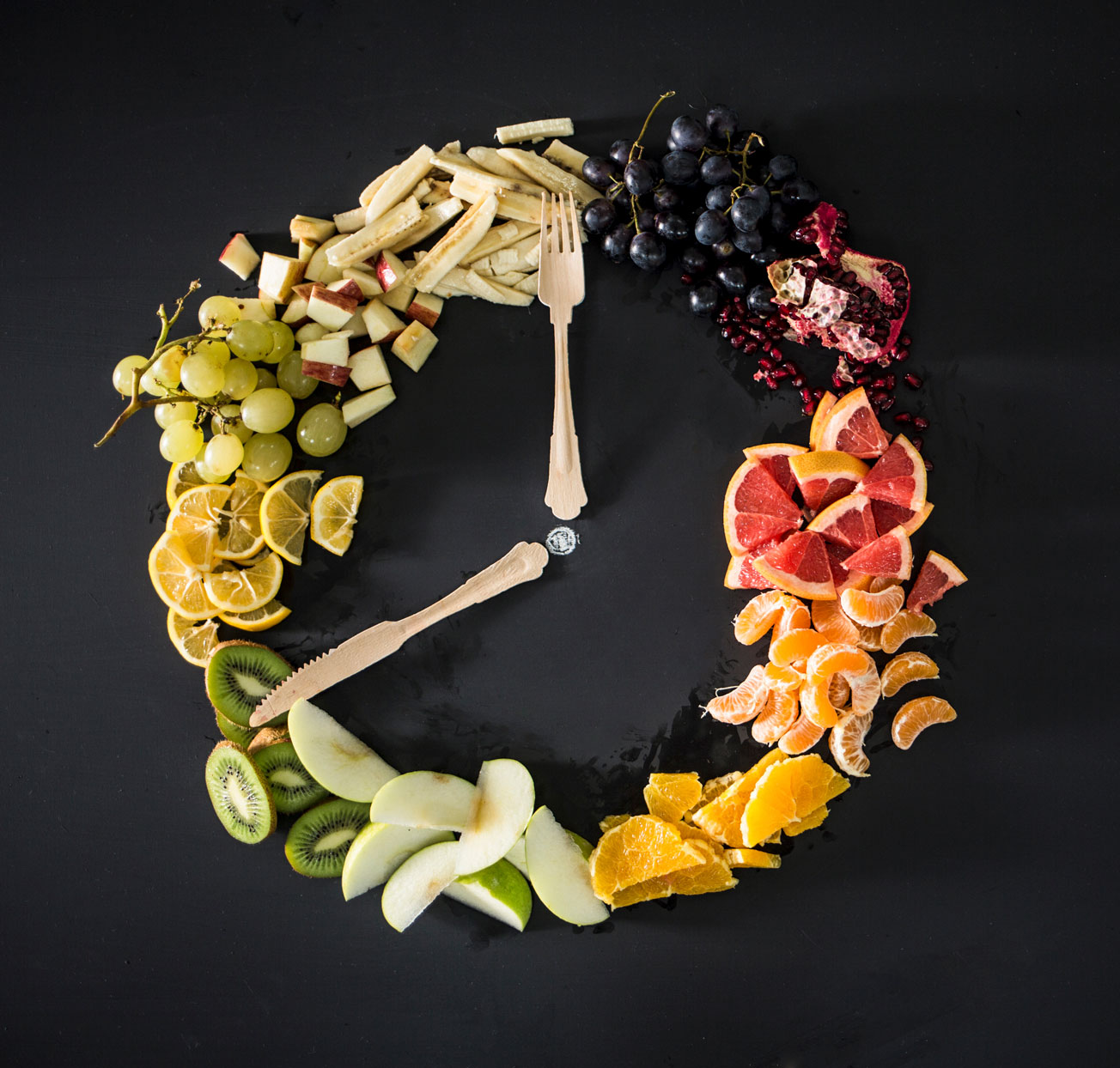 overhead shot of rainbow fruit in a circle with fork and spoon making clock hands to show time