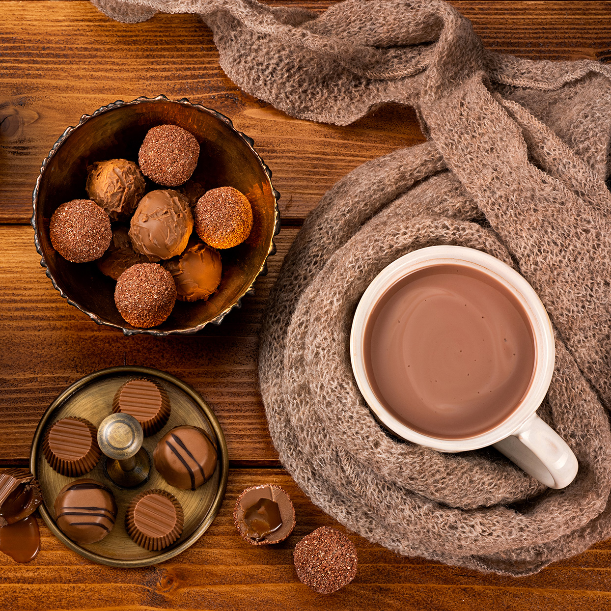 A mug of hot chocolate wrapped in a scarf and a plate of truffles