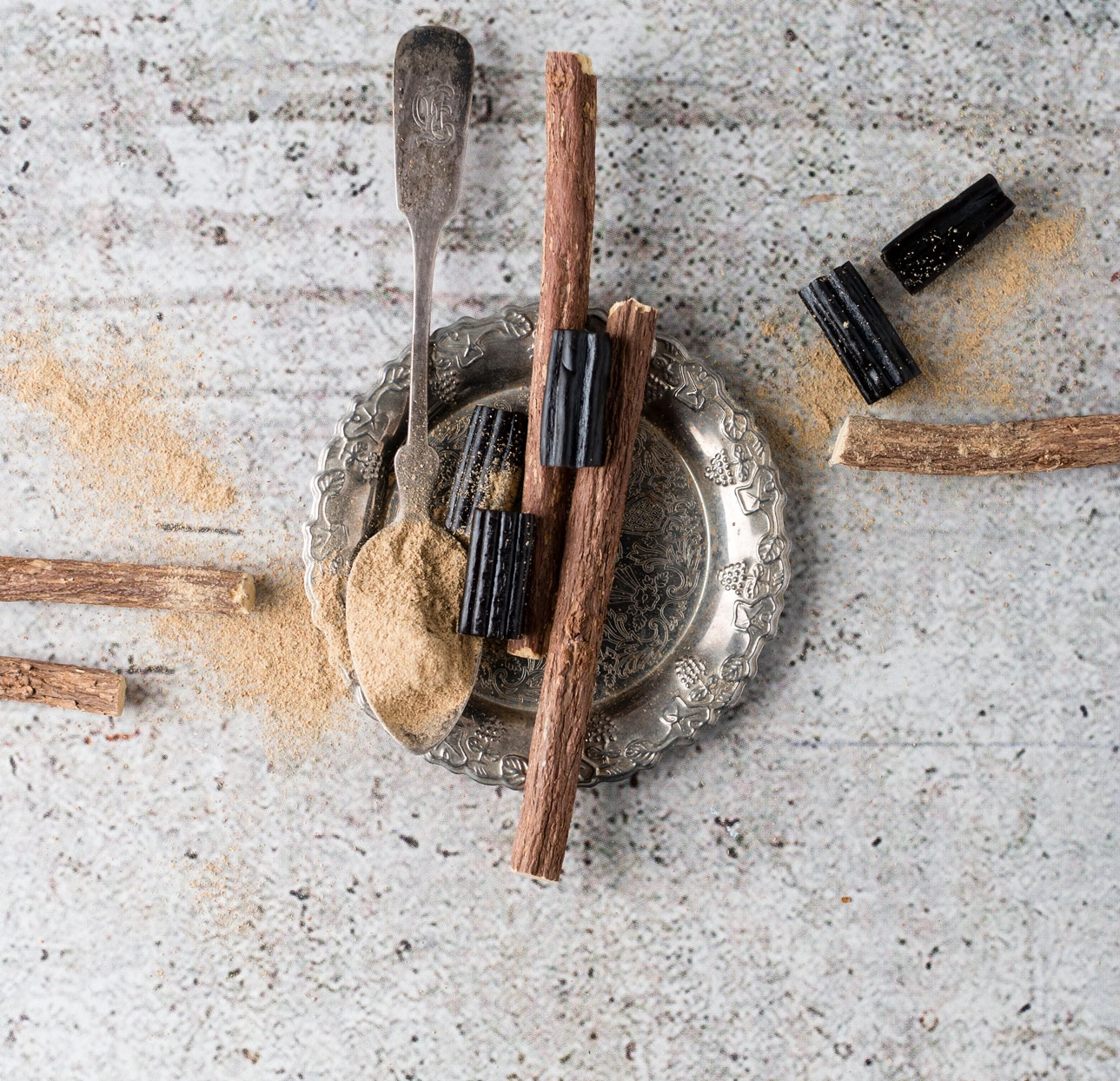 overhead shot of licorice roots, licorice powder and liorice candy on concrete background