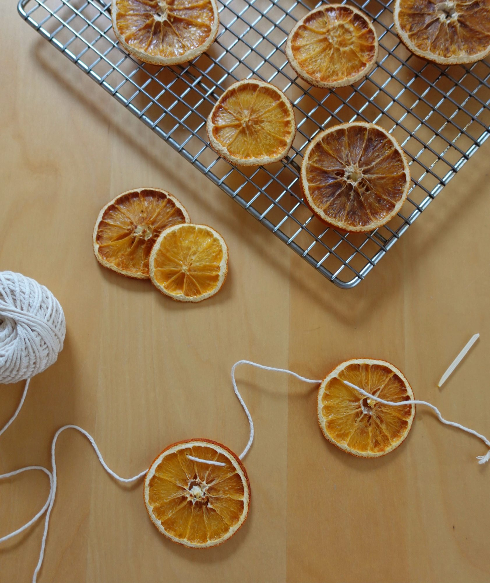 threading dried oranges on string to make a garland