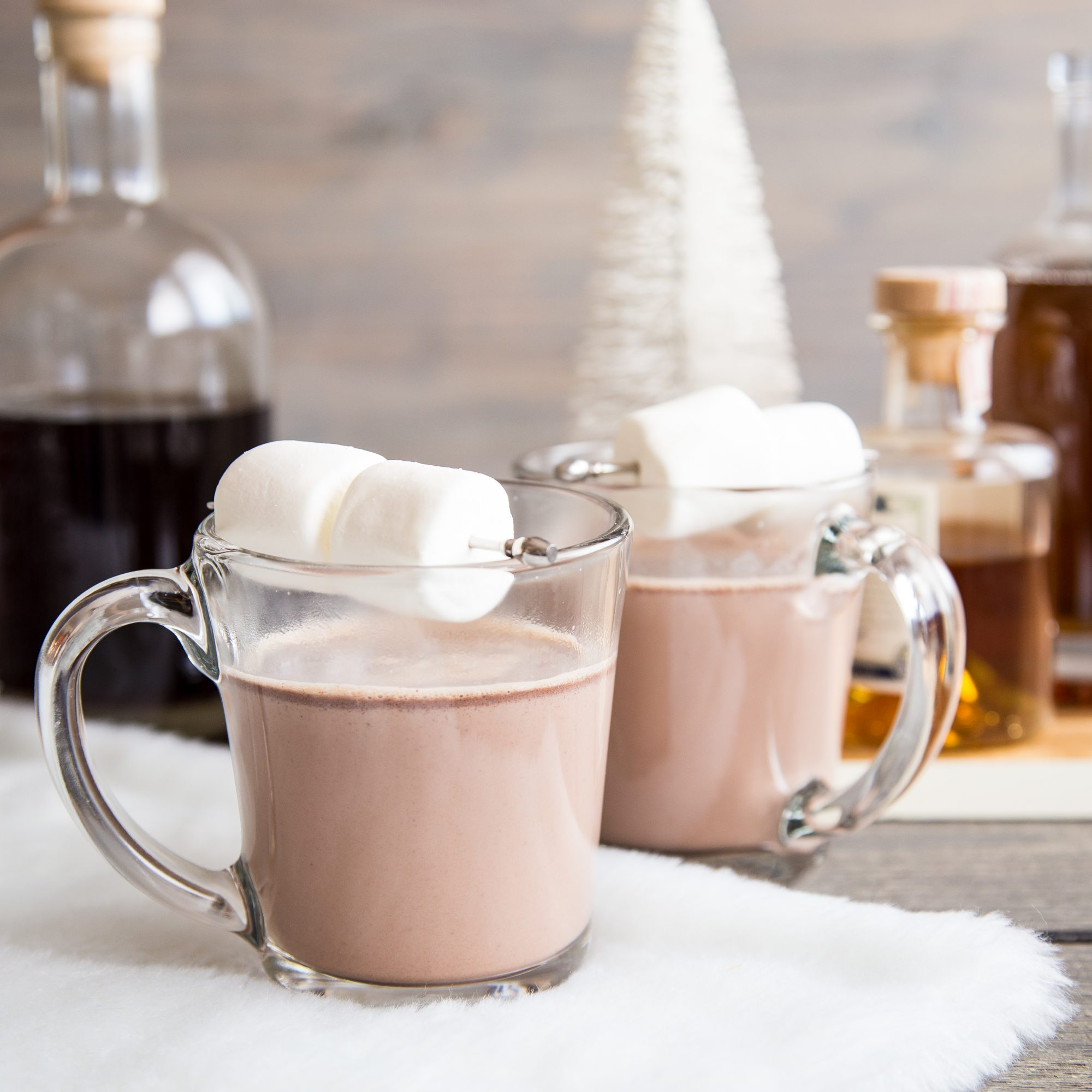 two mugs of spiked hot chocolate with with marshmallows on top and bottles in the background
