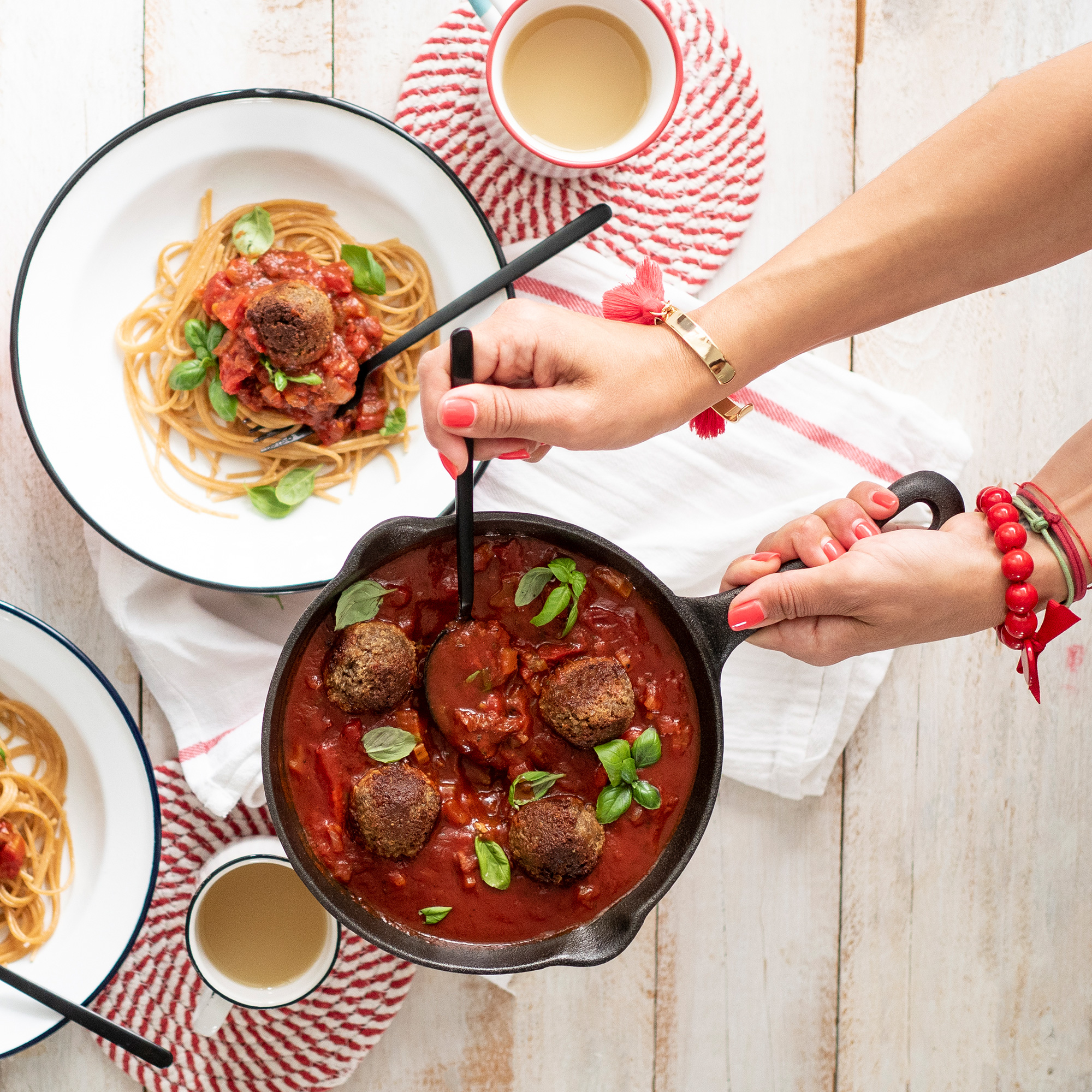 A woman's hands cooking spaghetti and meatballs in a skillet