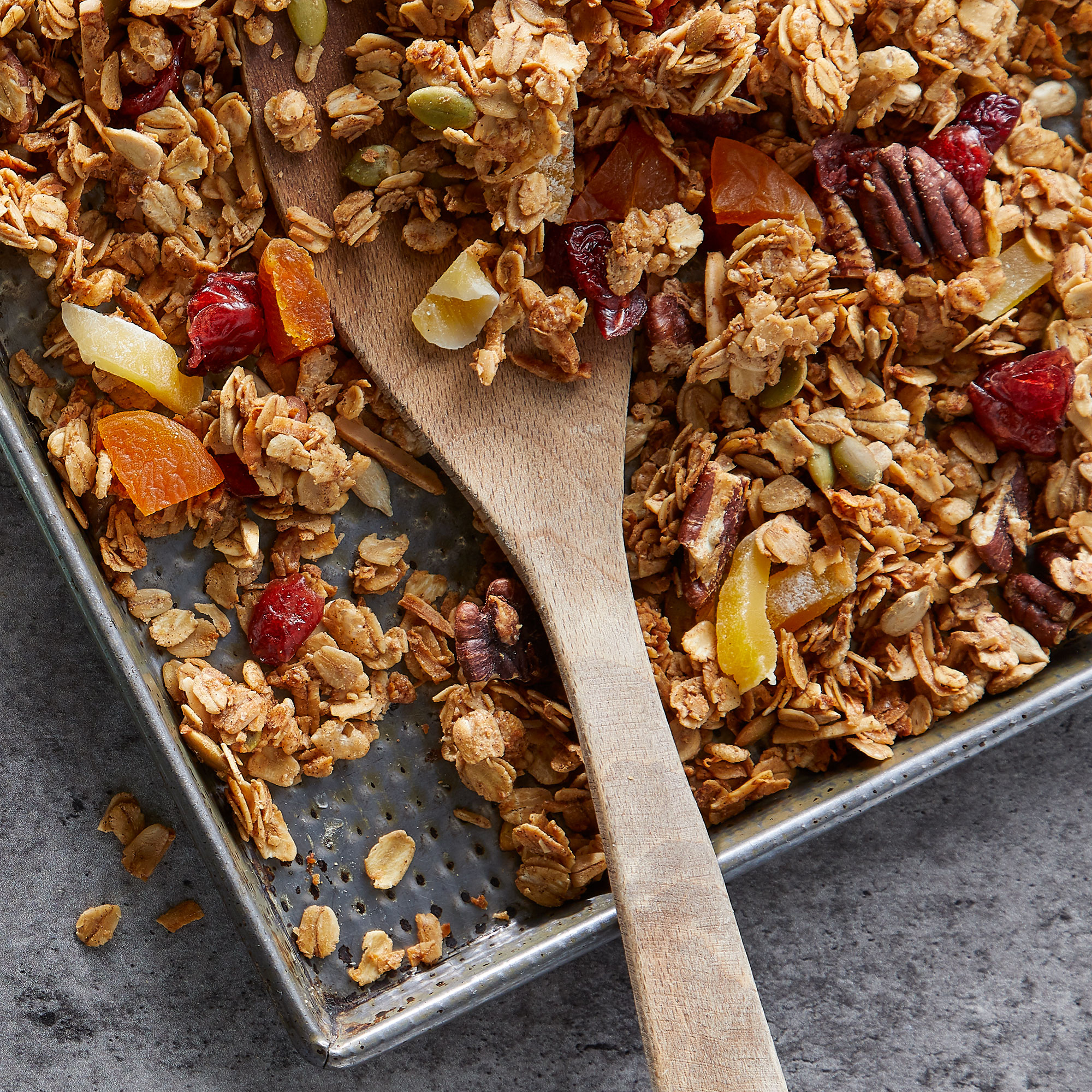 granola on a baking sheet with a wooden spoon