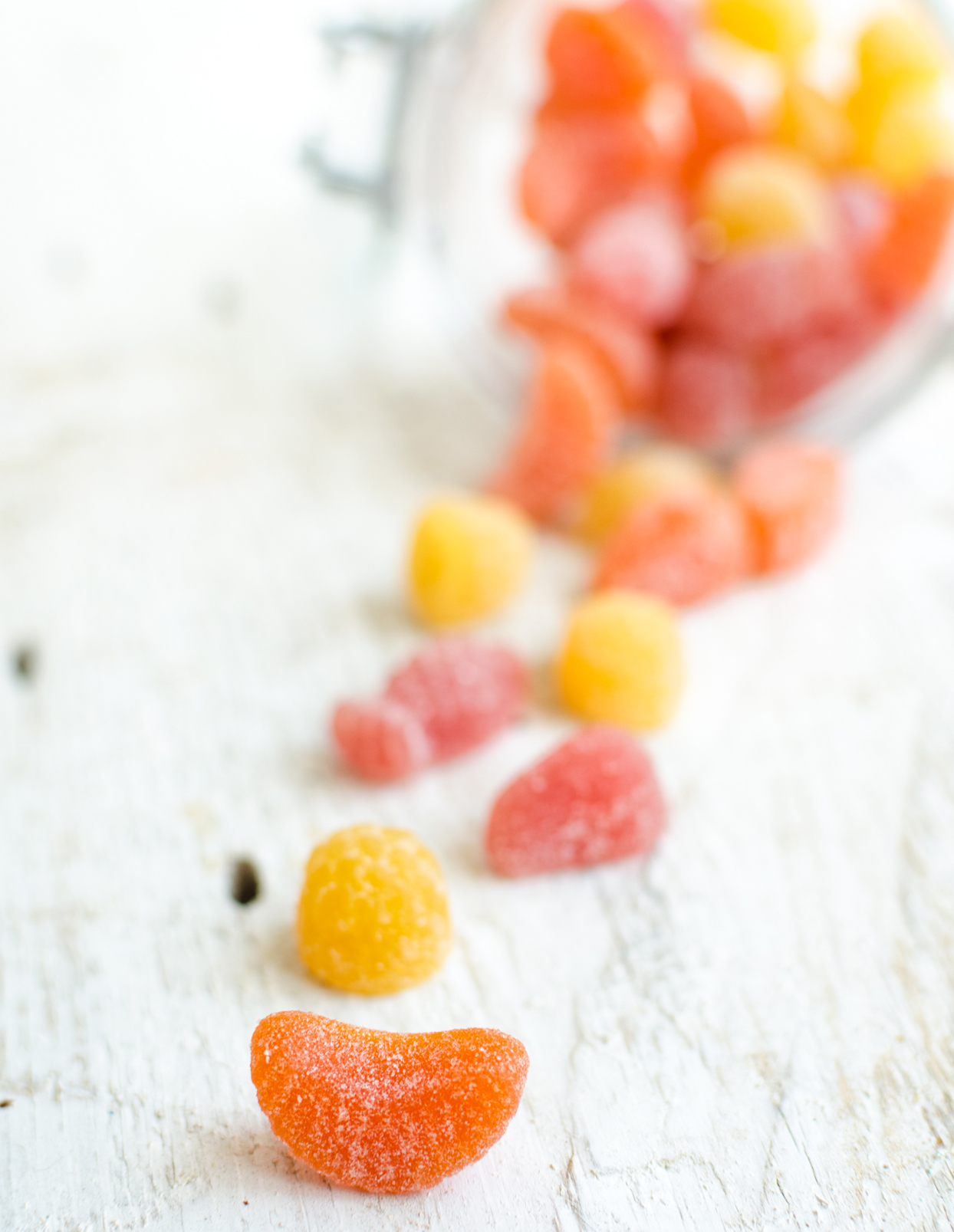 red, yellow and orange gummy vitamins pouring out of a glass jar on a white wooden background