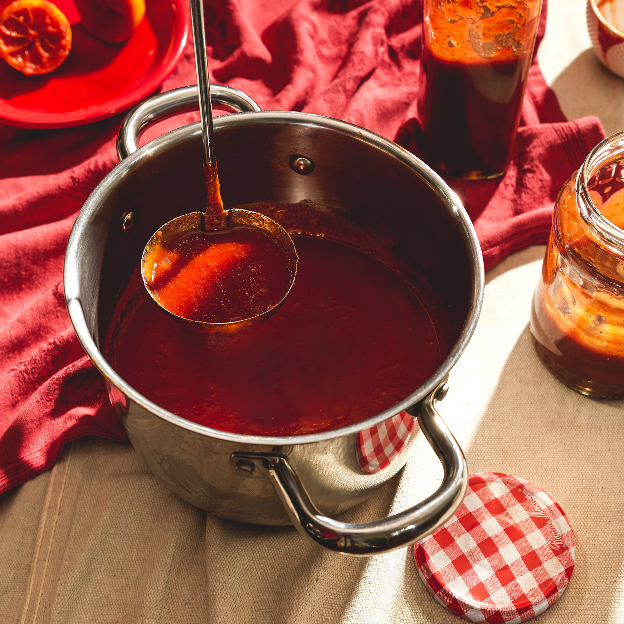 A pot of homemade barbecue sauce with jars of sauce