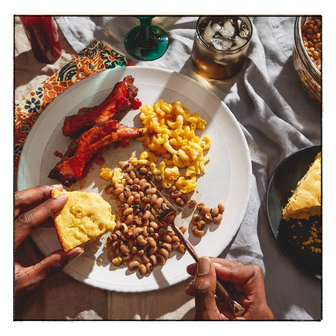 A plate with black-eyed peas, cornbread, ribs and mac and cheese