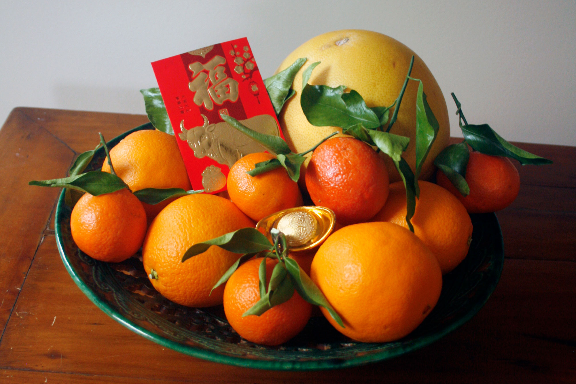A bowl of citrus fruits with a lucky envelope and ingot