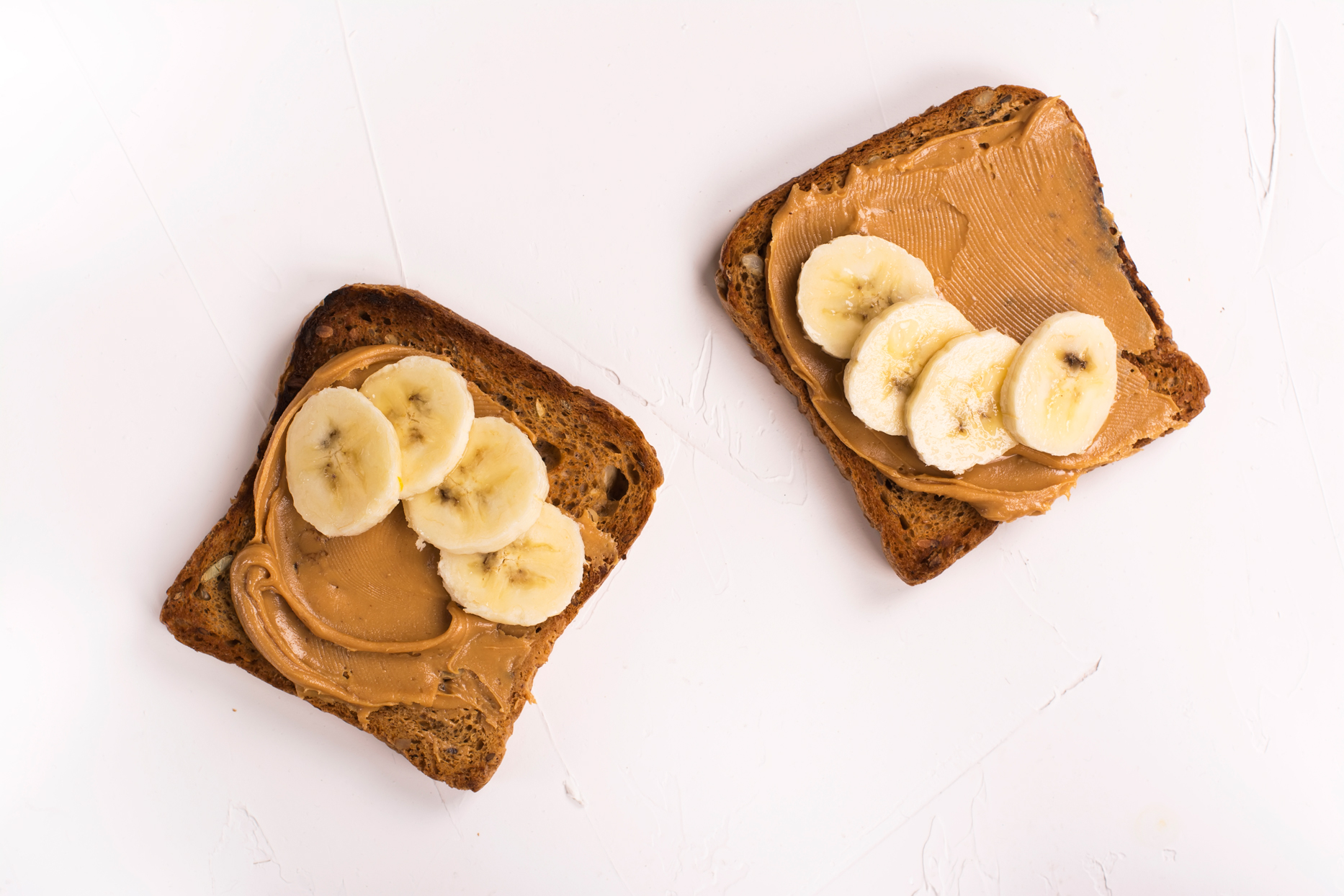 whole grain toast with peanut butter and banana slices on white background