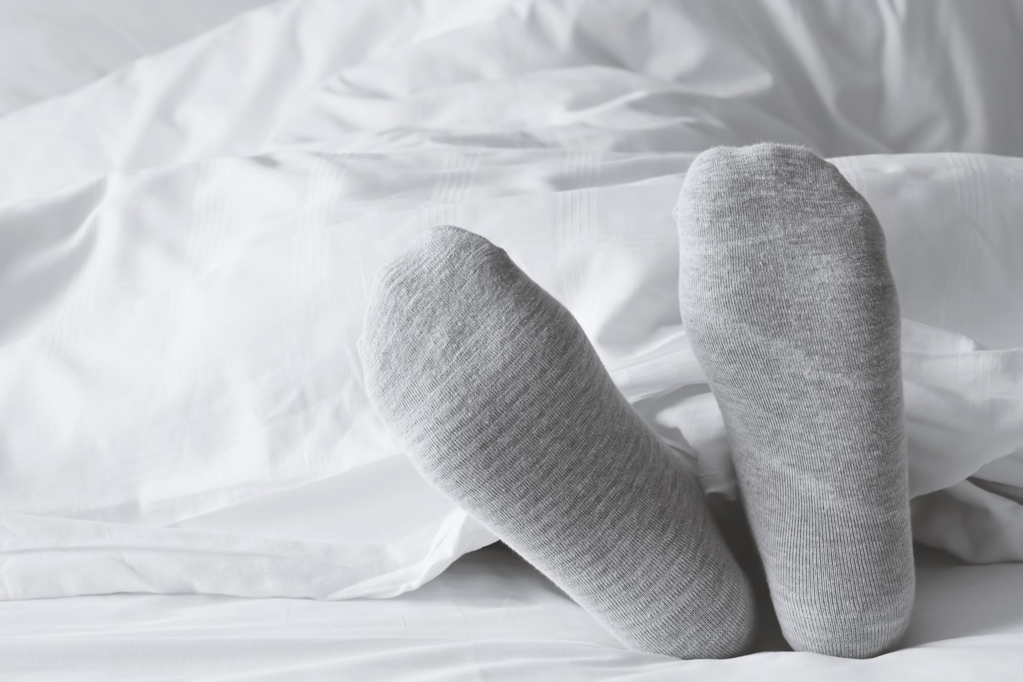 person wearing socks in bed