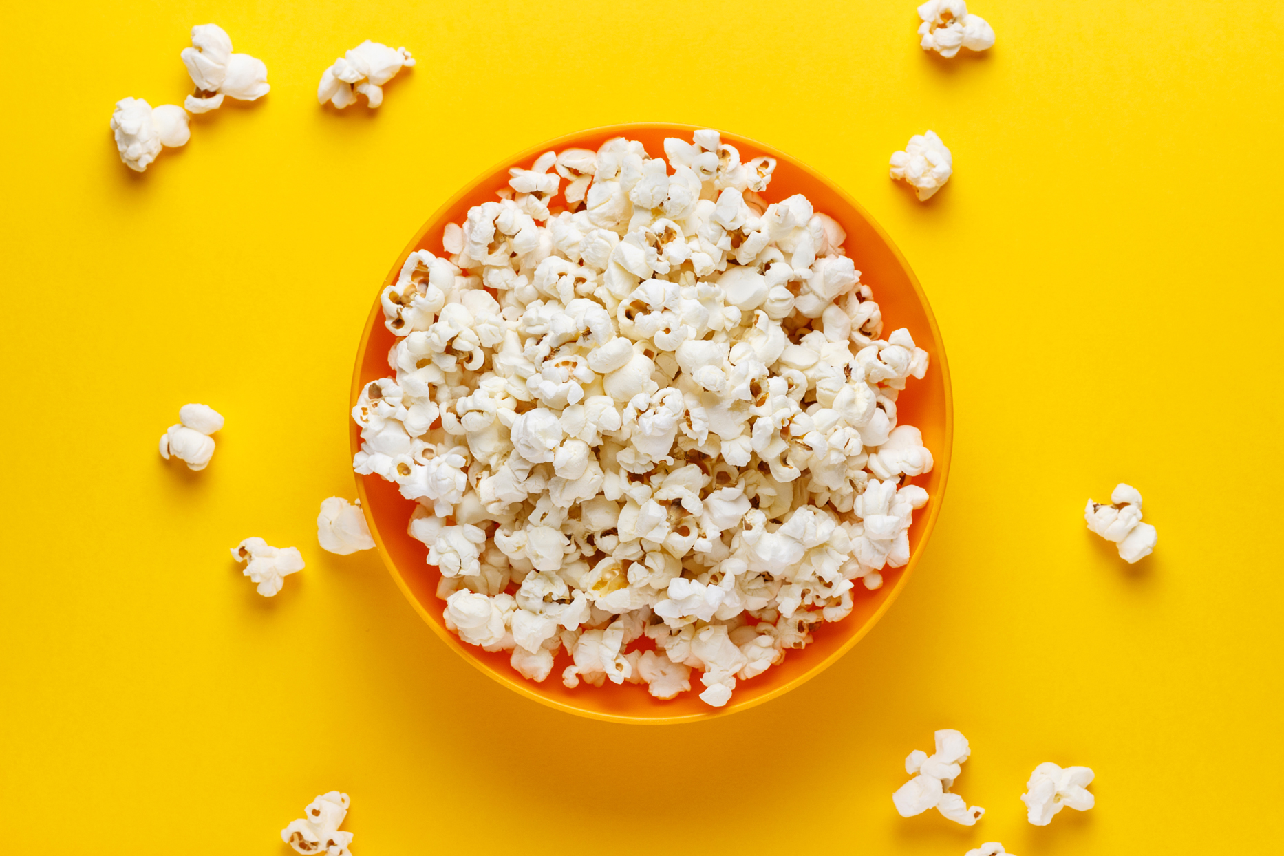 popcorn in orange bowl on yellow background