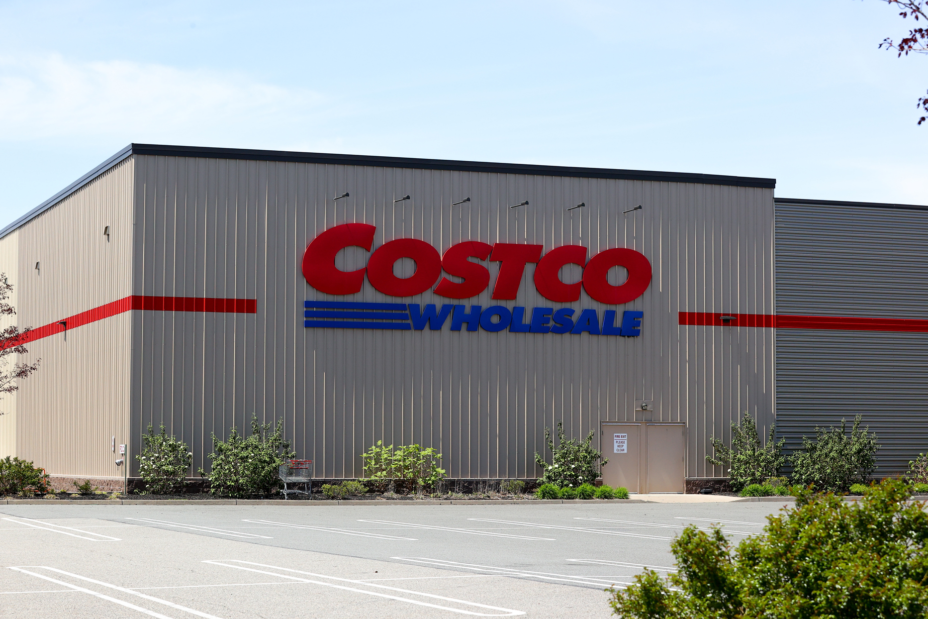 costco storefront with bushes and parking lot in front
