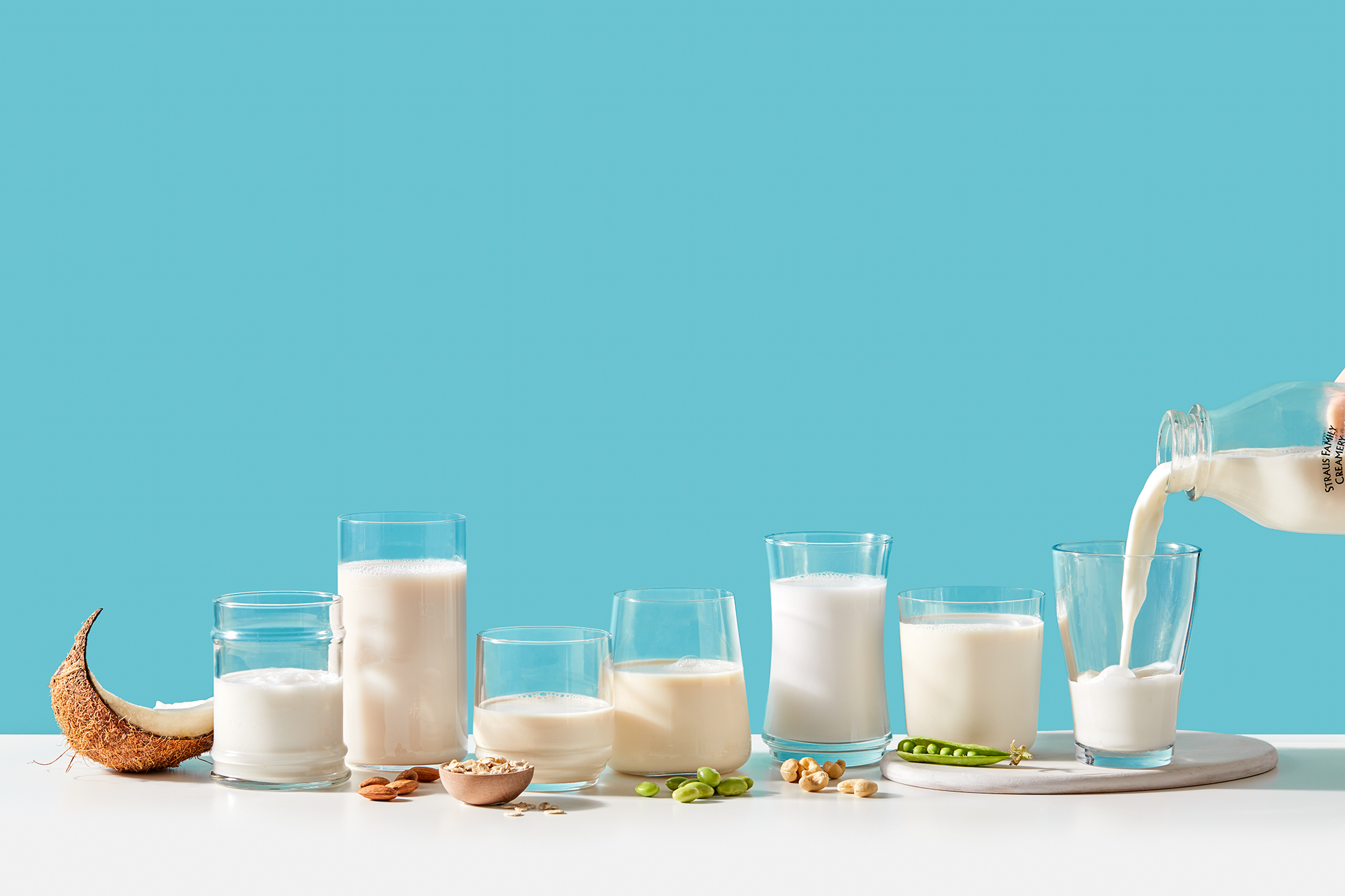 Seven glasses of dairy alternative milks on a blue background
