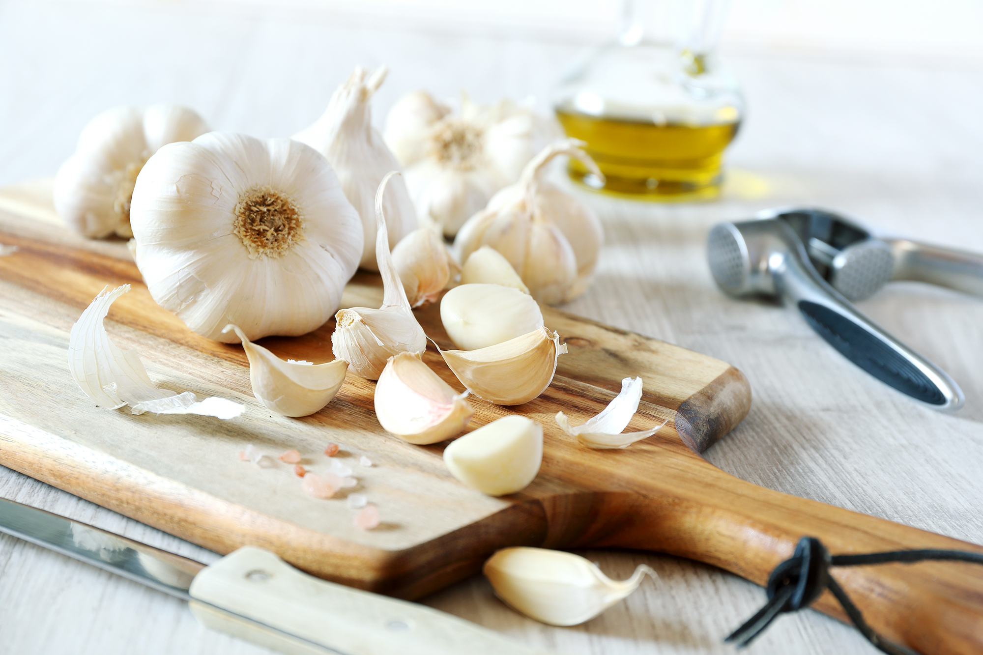 Bulbs of garlic, garlic press and olive oil