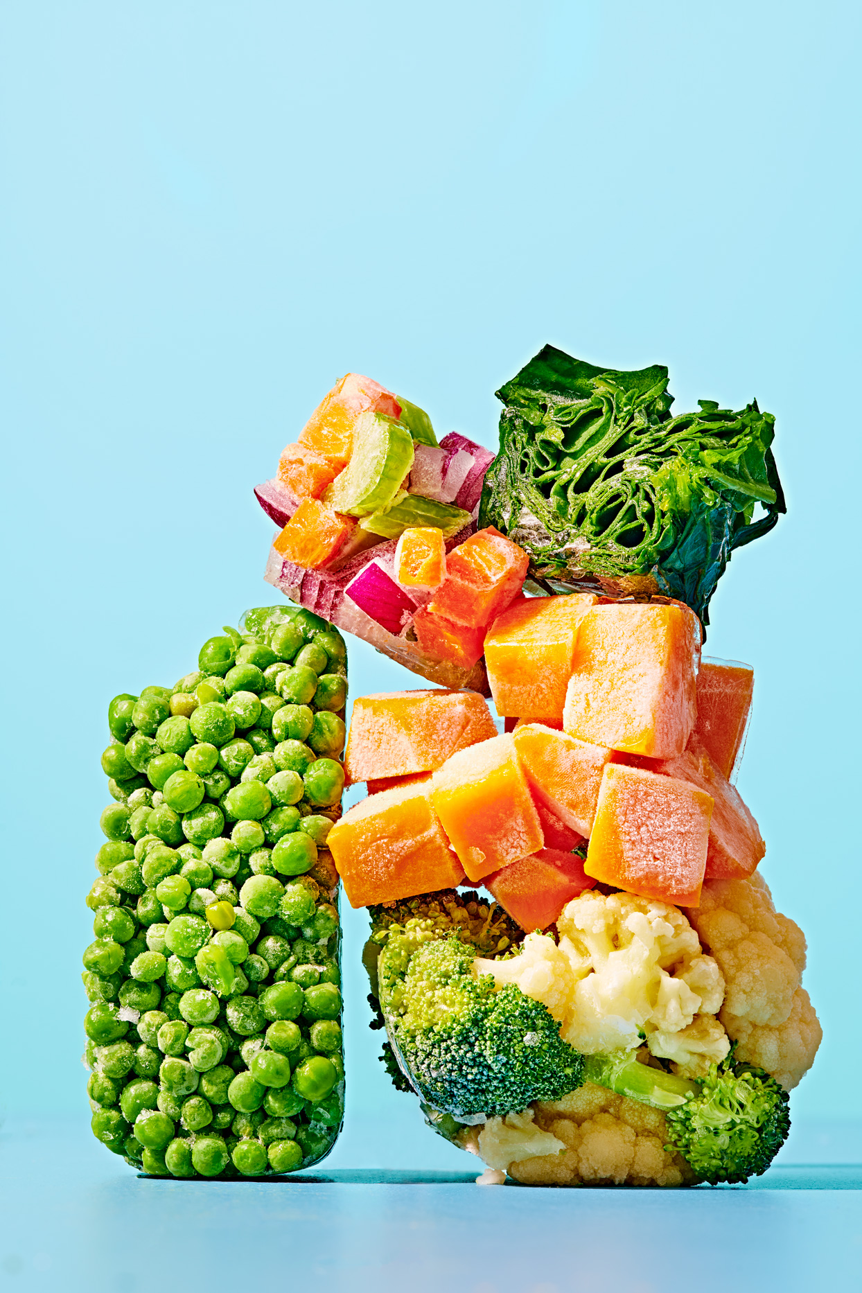 frozen vegetables including peas, corn and spinach stacked on a blue background
