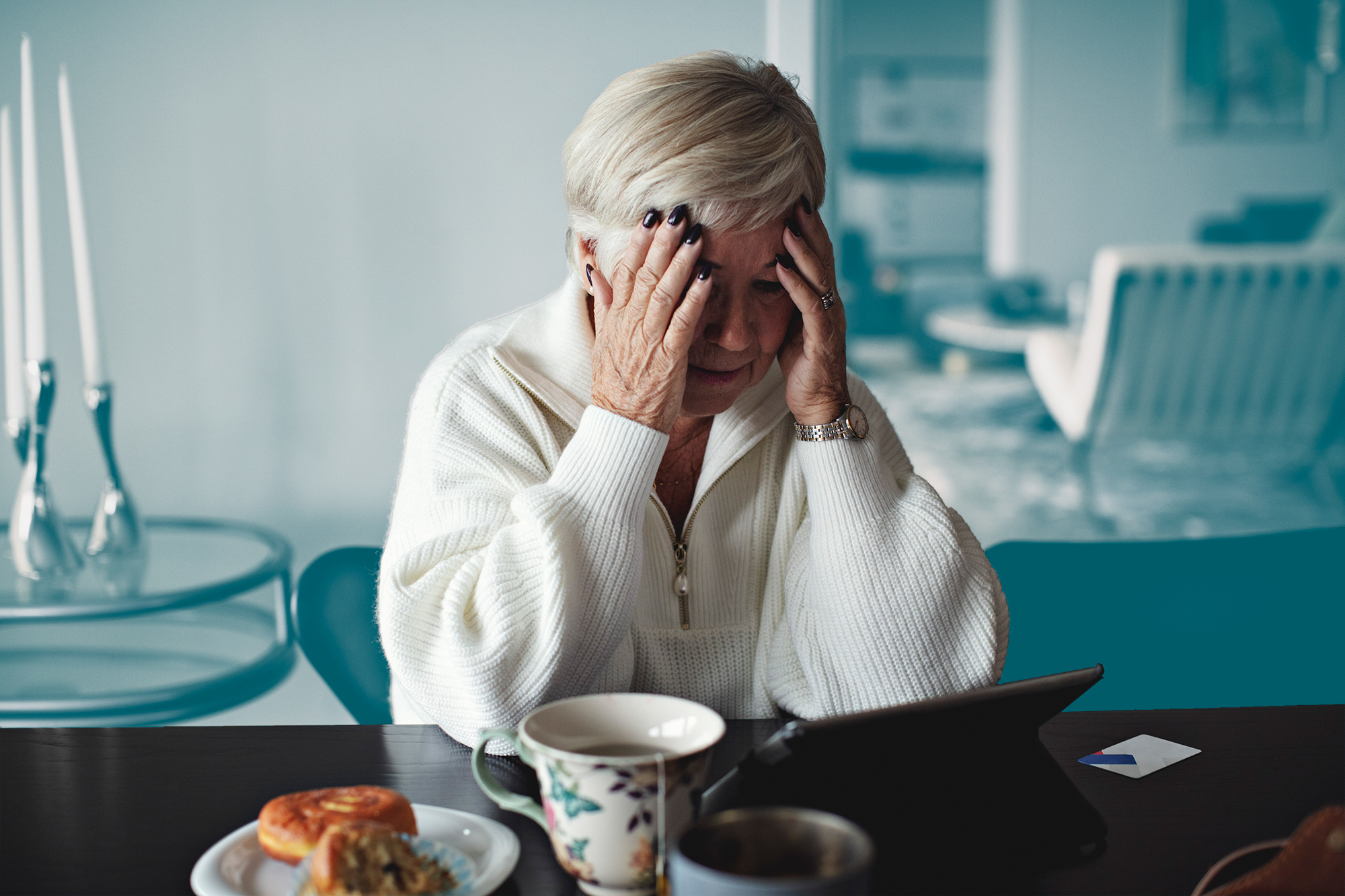 Worried senior woman with head in hands sitting by dining table at home