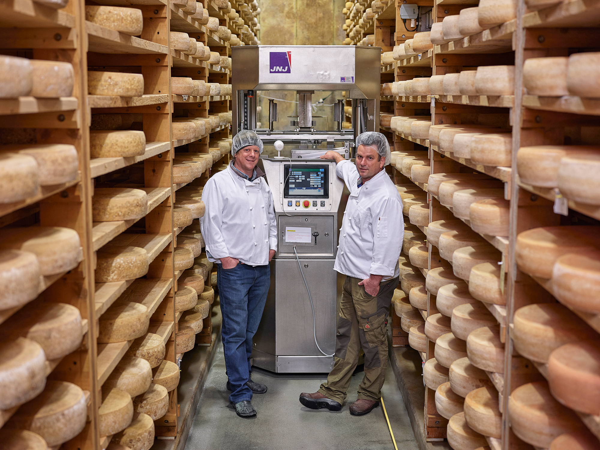 two men standing in a cheese factory