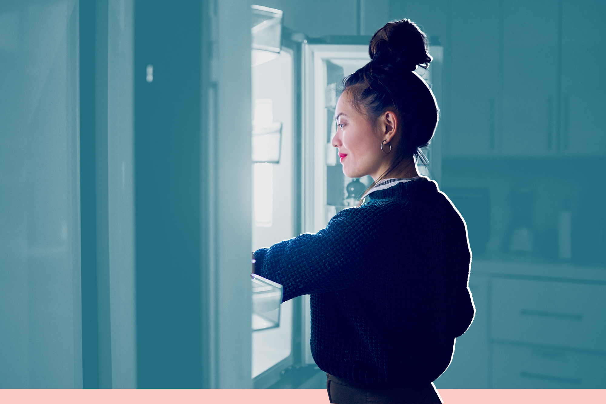 woman looking in a refrigerator at night