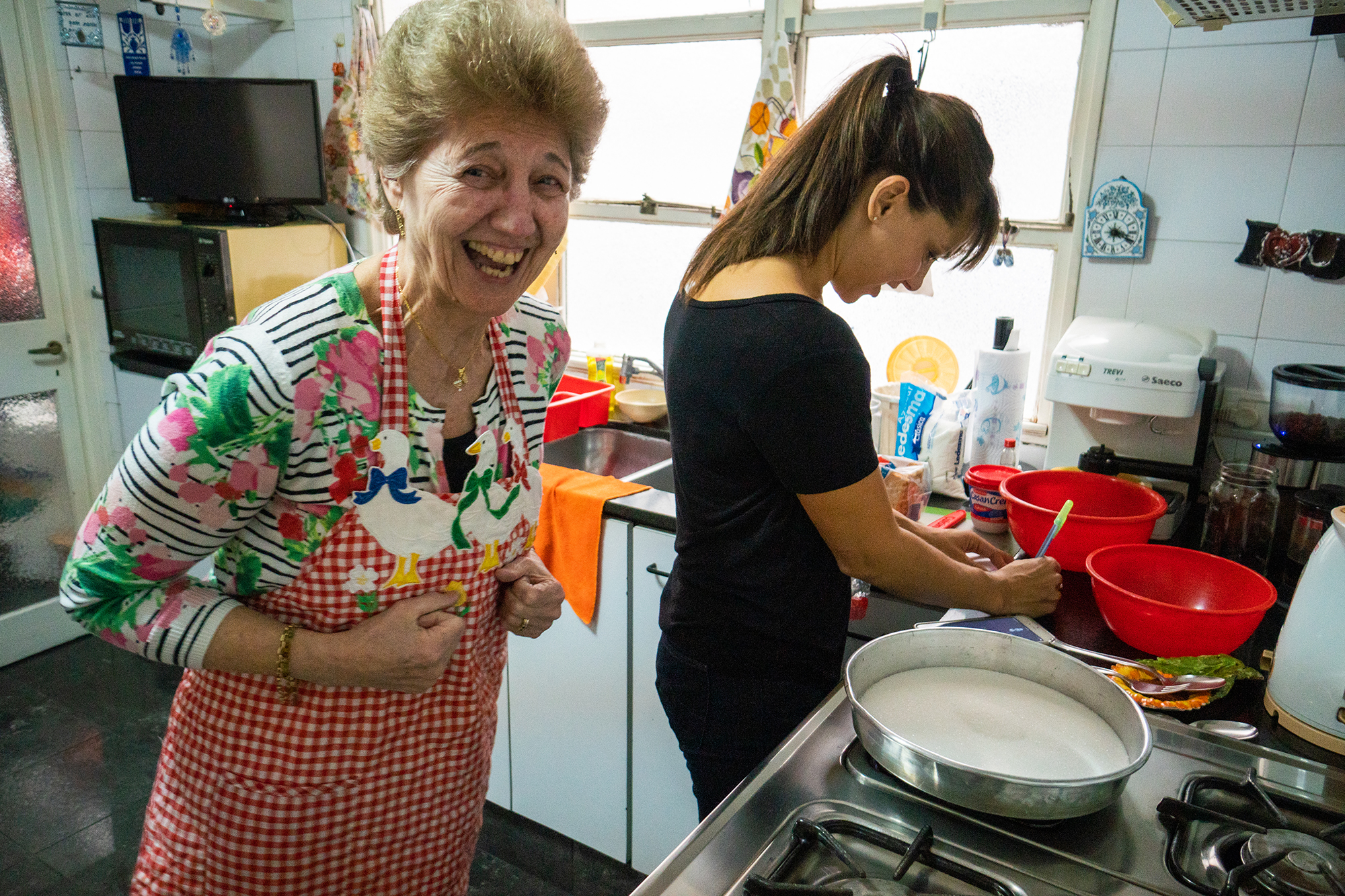 An older and a younger woman cooking together in a kitchen
