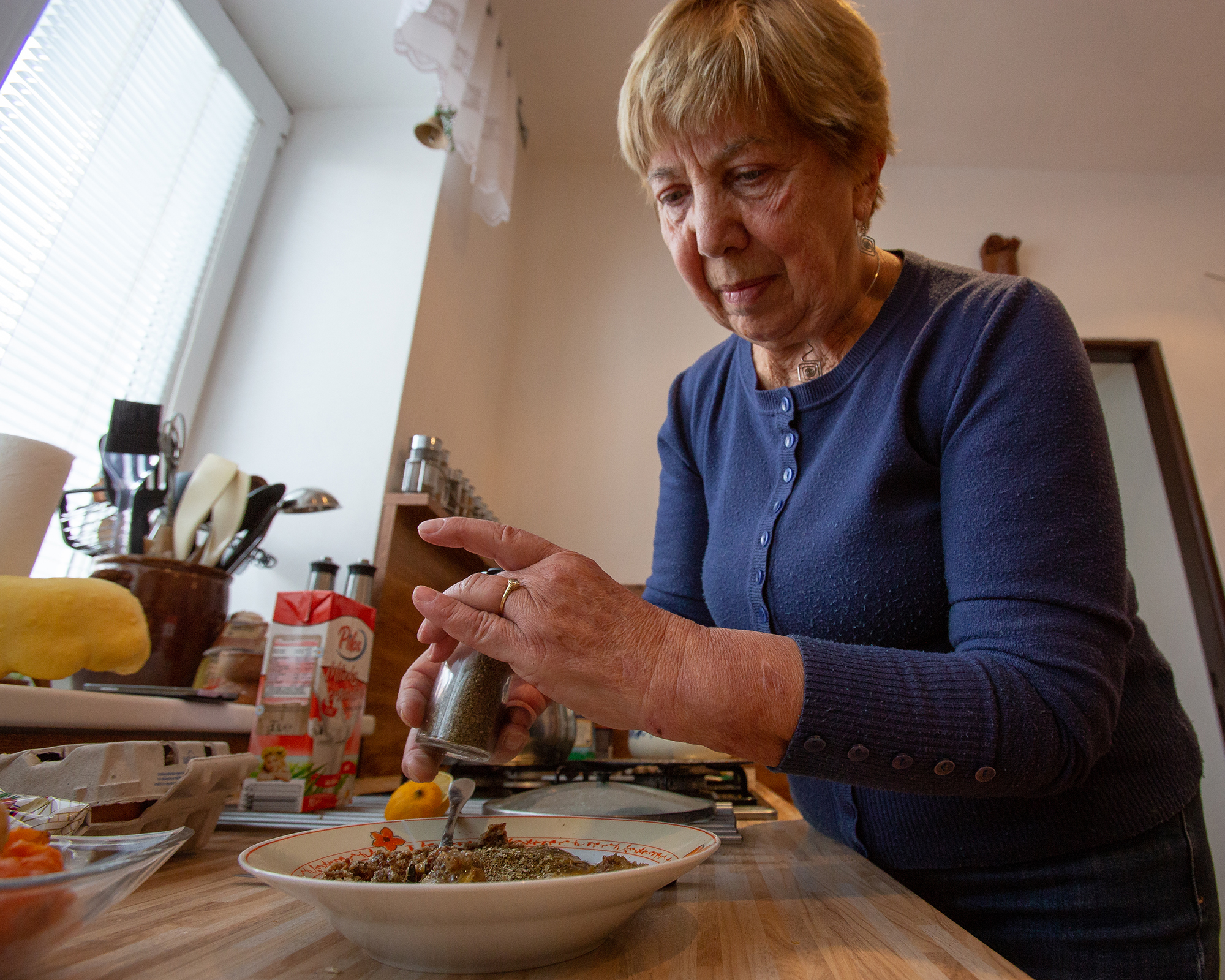 older woman grinding pepper onto a bowl of food
