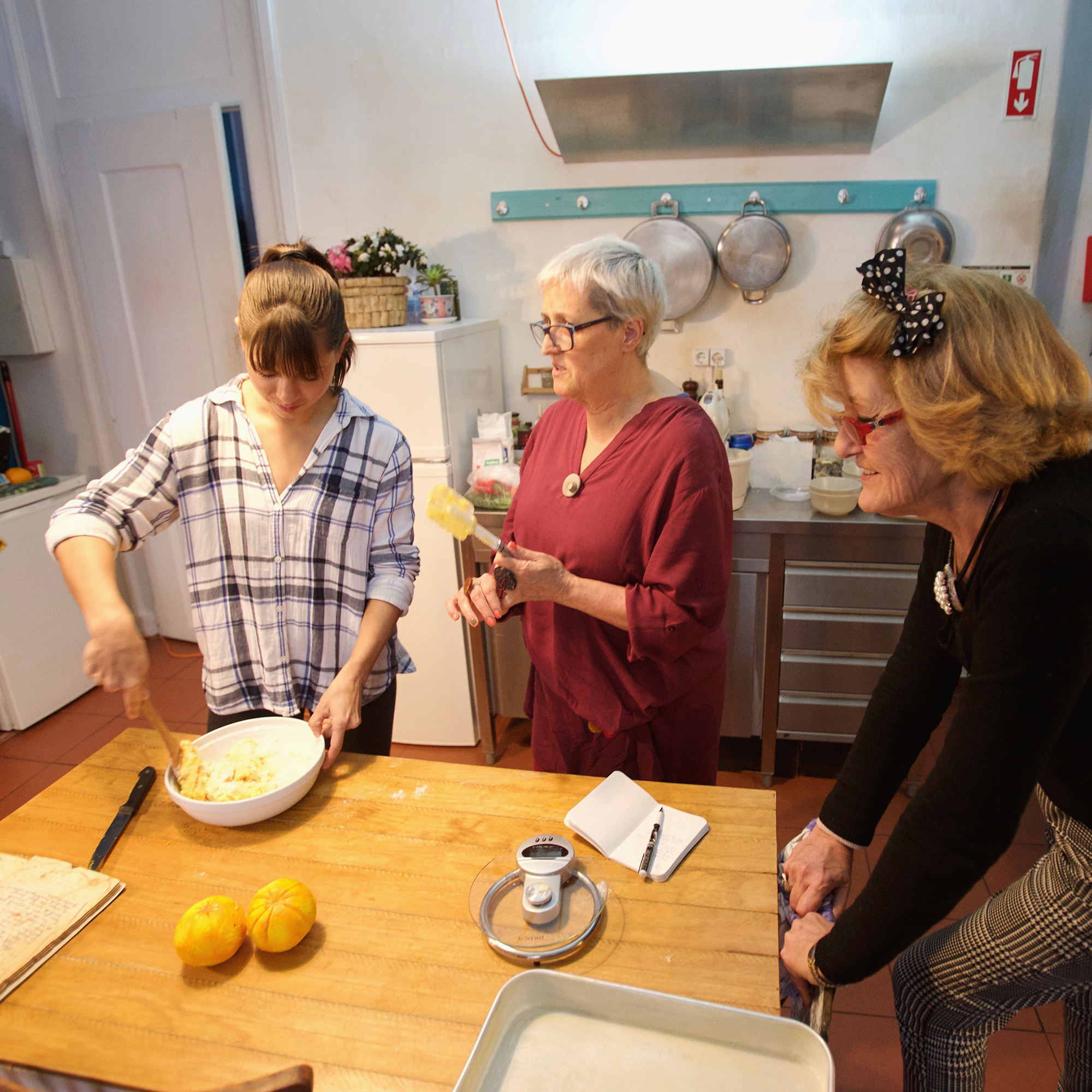 3 women cooking together in a kitchen