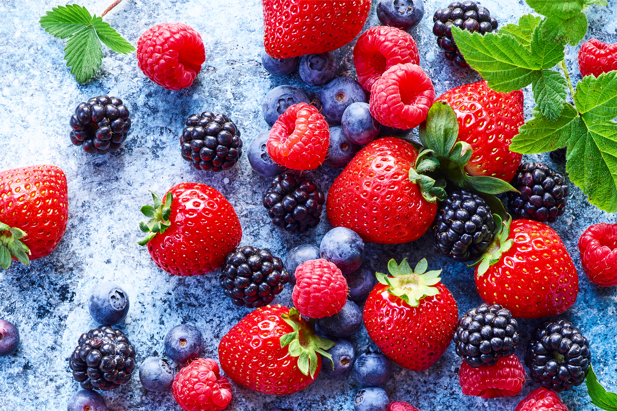 Mixed berries on a textured blue and white background