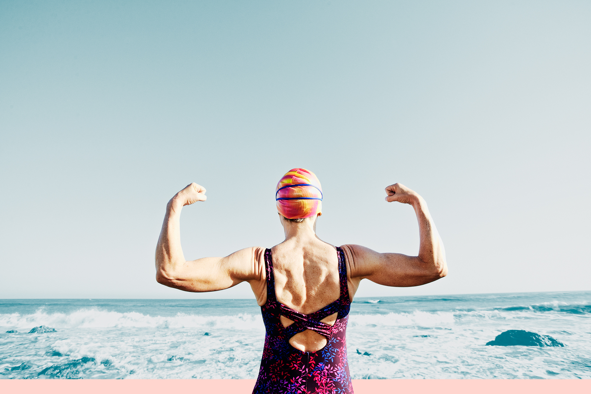 Older woman flexing her muscles on beach