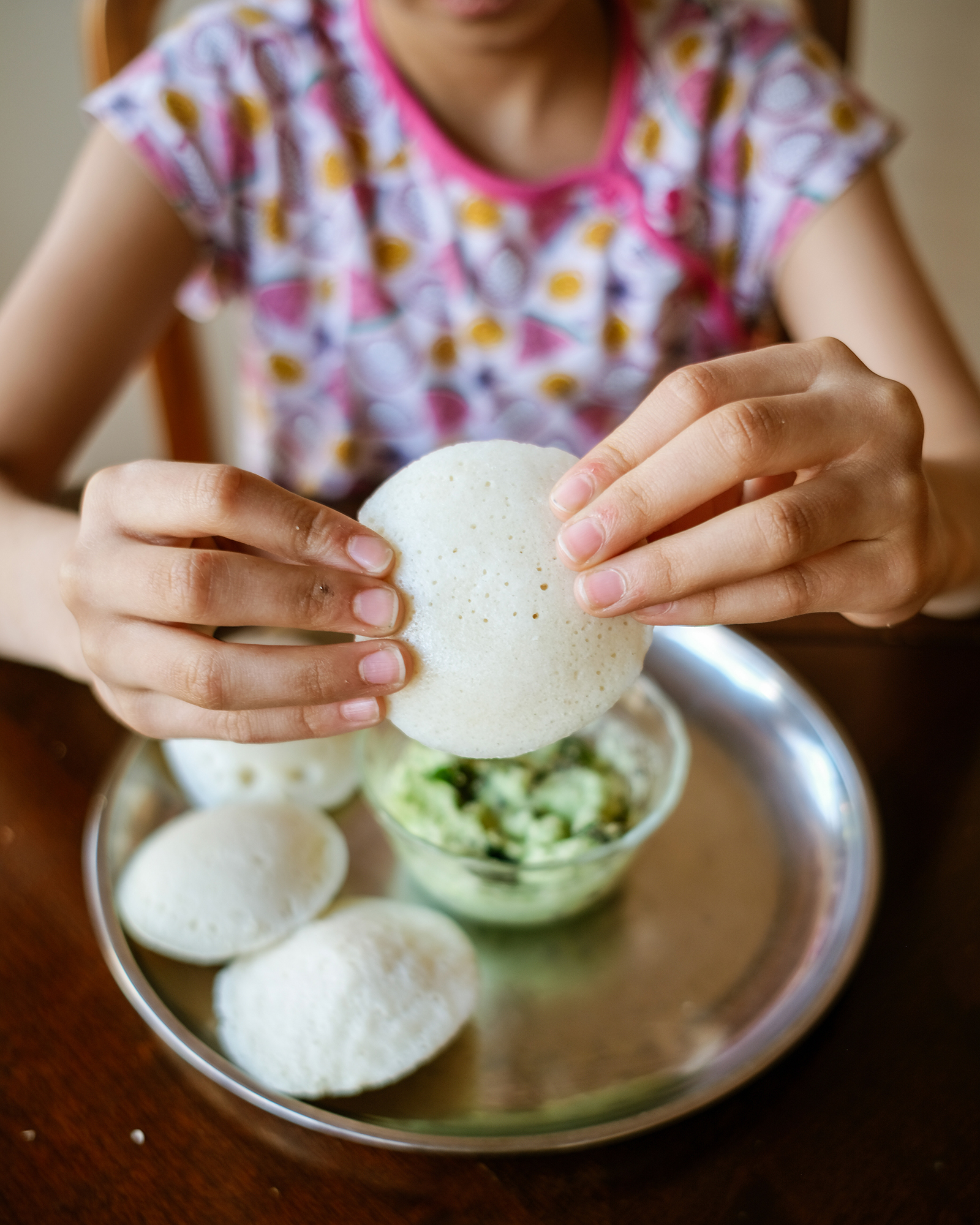 hands holding a piece of Idli