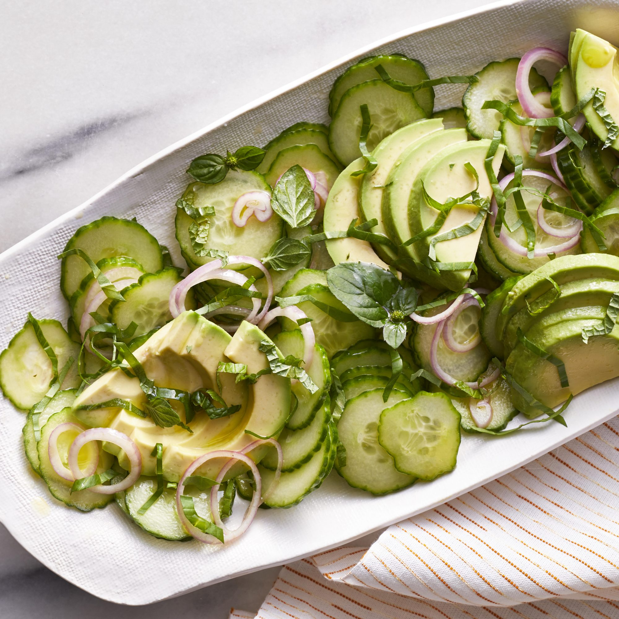 a white platter with cucumbers and avocados