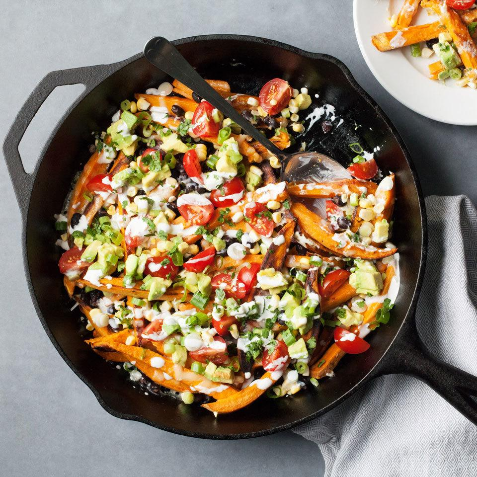 a cast iron skillet with sweet potatoes and various toppings