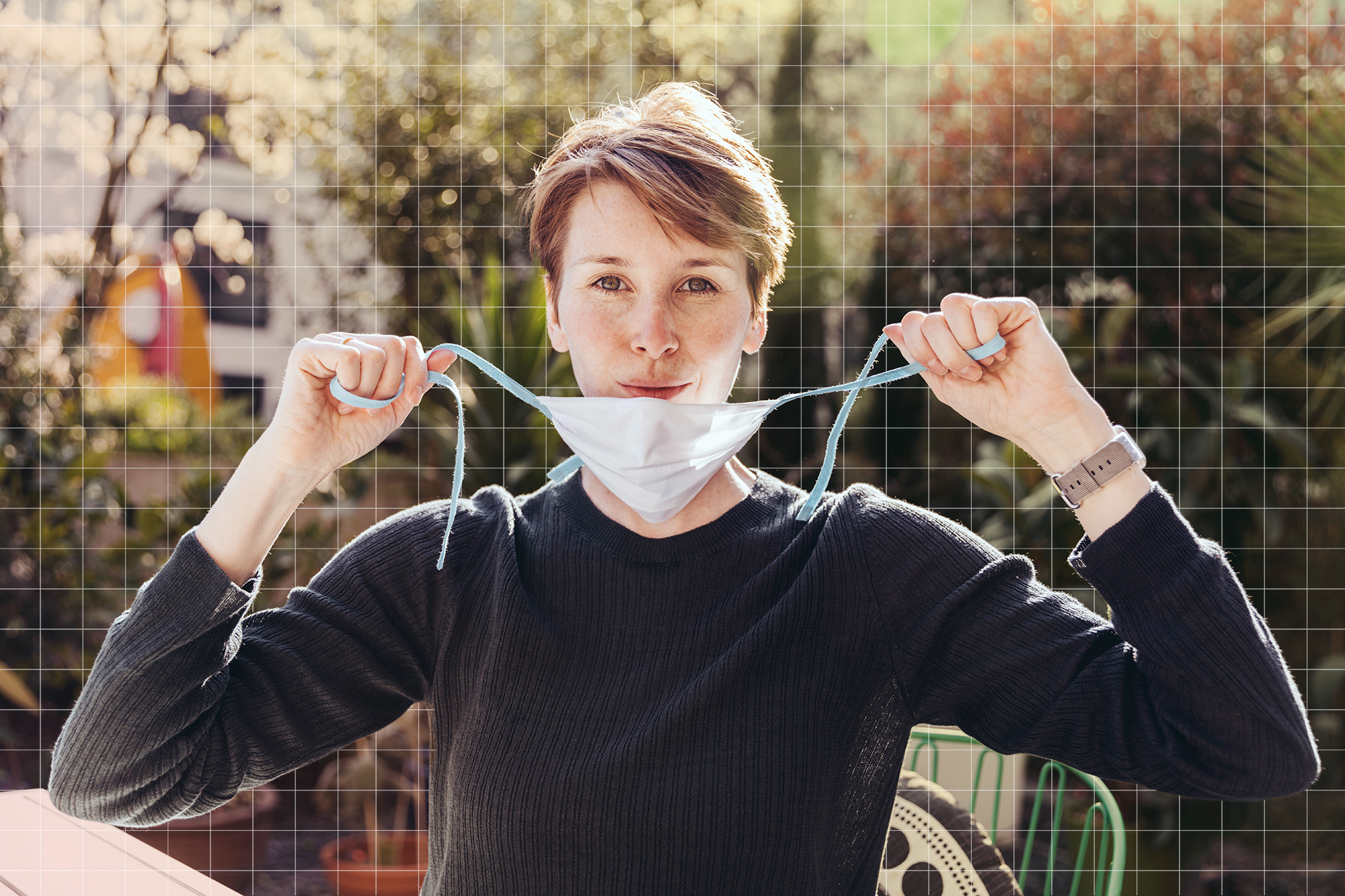 Woman siting in garden, removing face mask