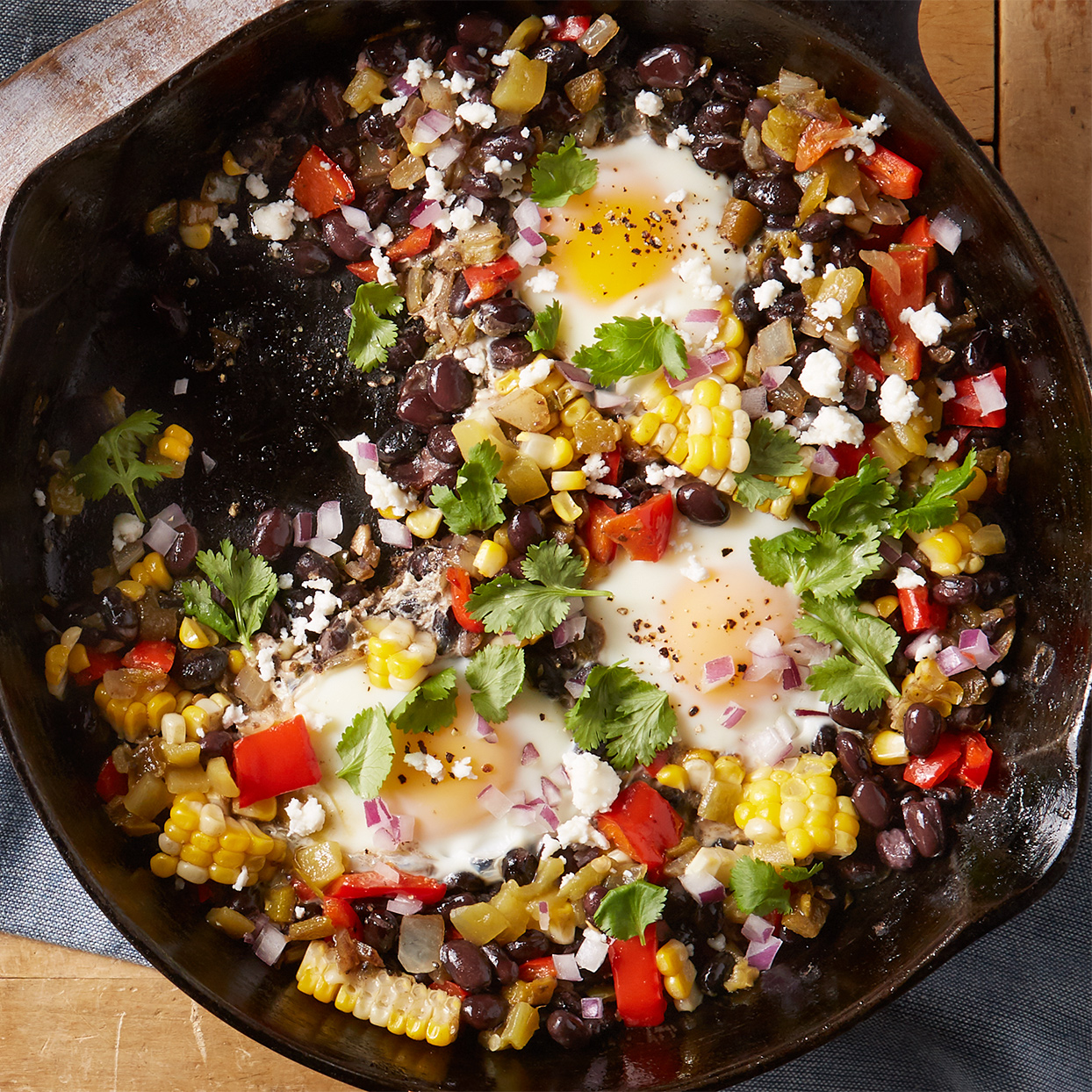 a cast iron skillet with black beans, corn and poached eggs
