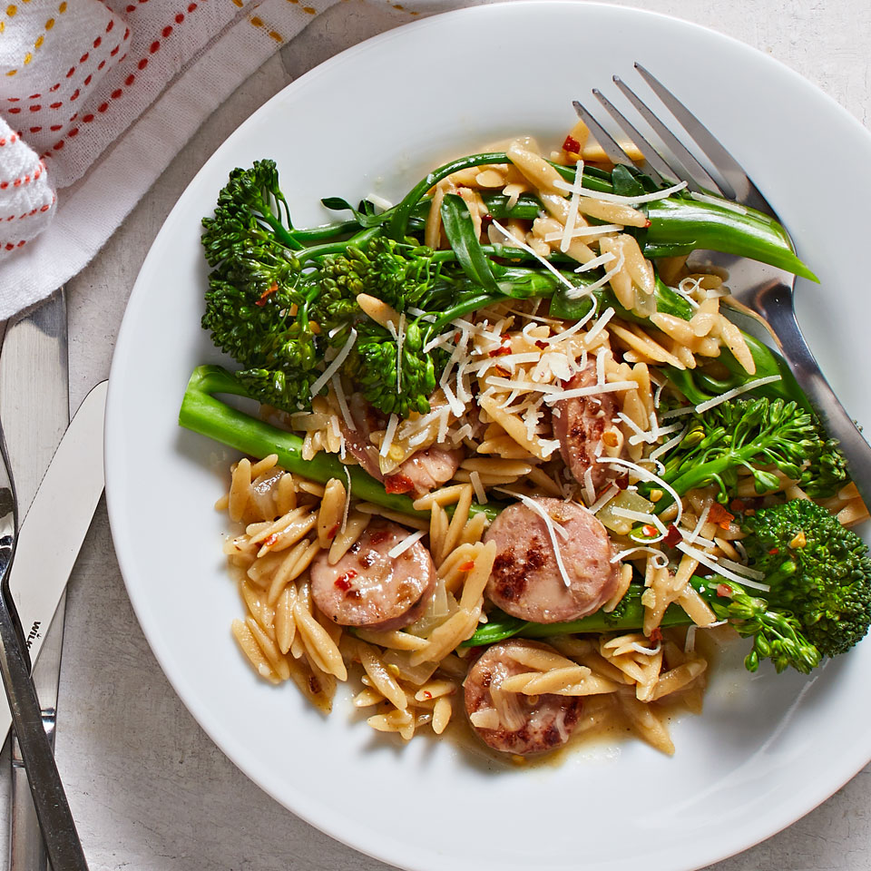 a bowl with orzo pasta, chicken sausage and broccolini