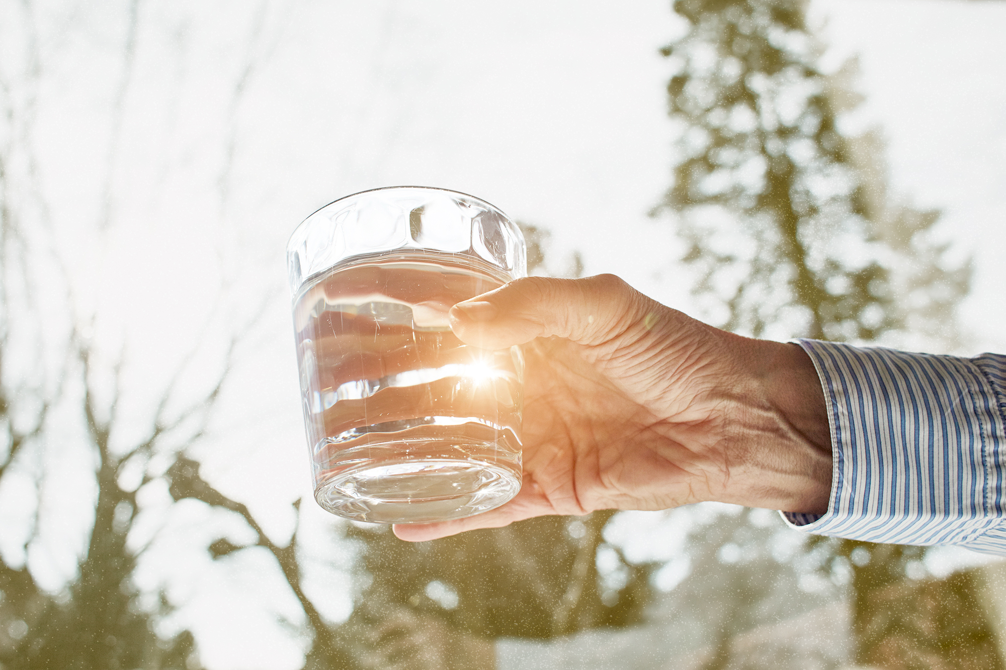 Senior woman holding glass of water, close-up