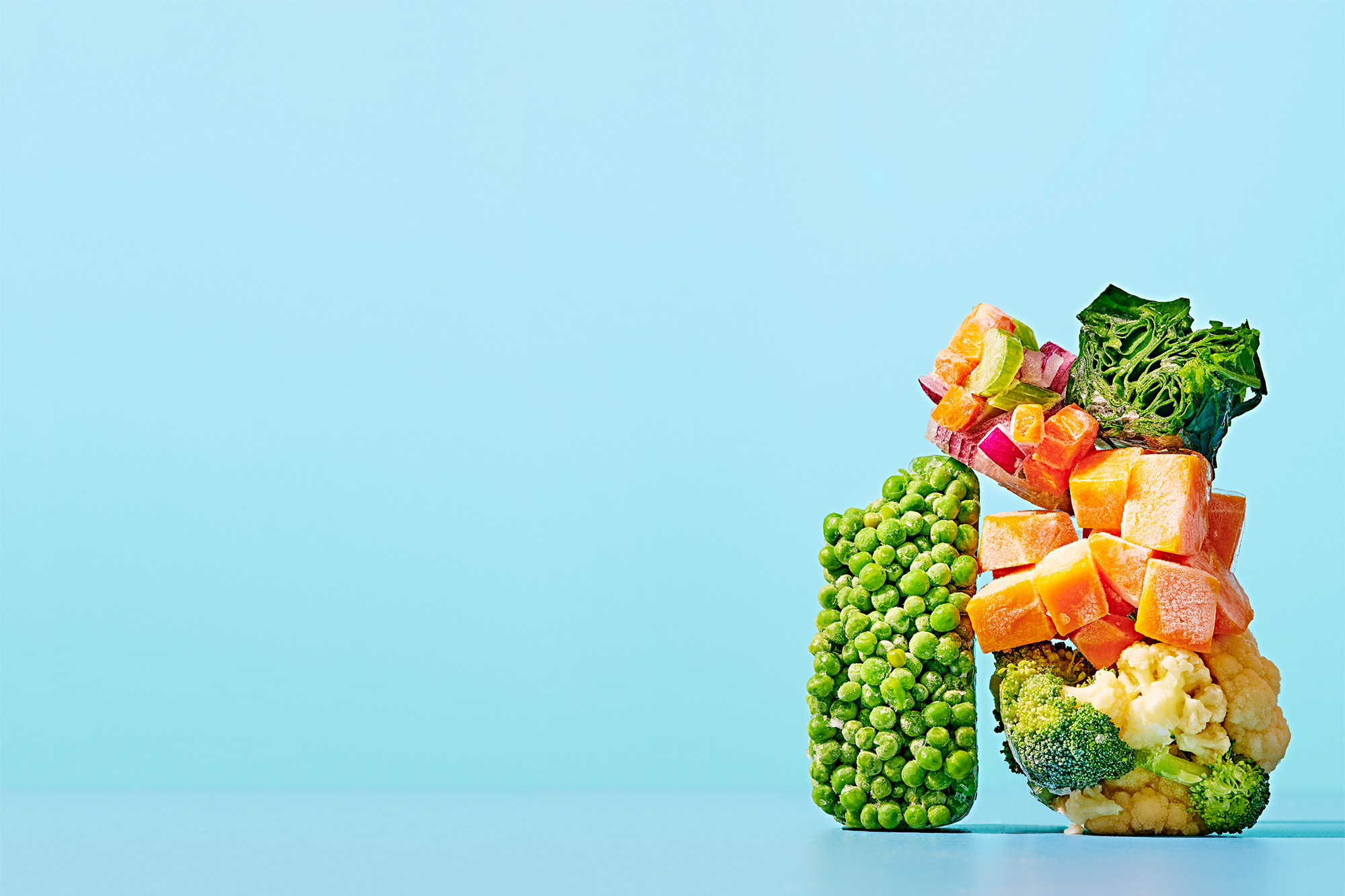 A stack of frozen vegetables on a blue background