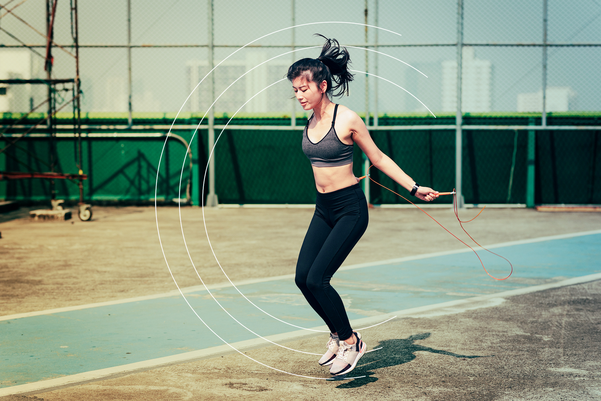 Fit Sportswoman Jumping the Rope Outdoors