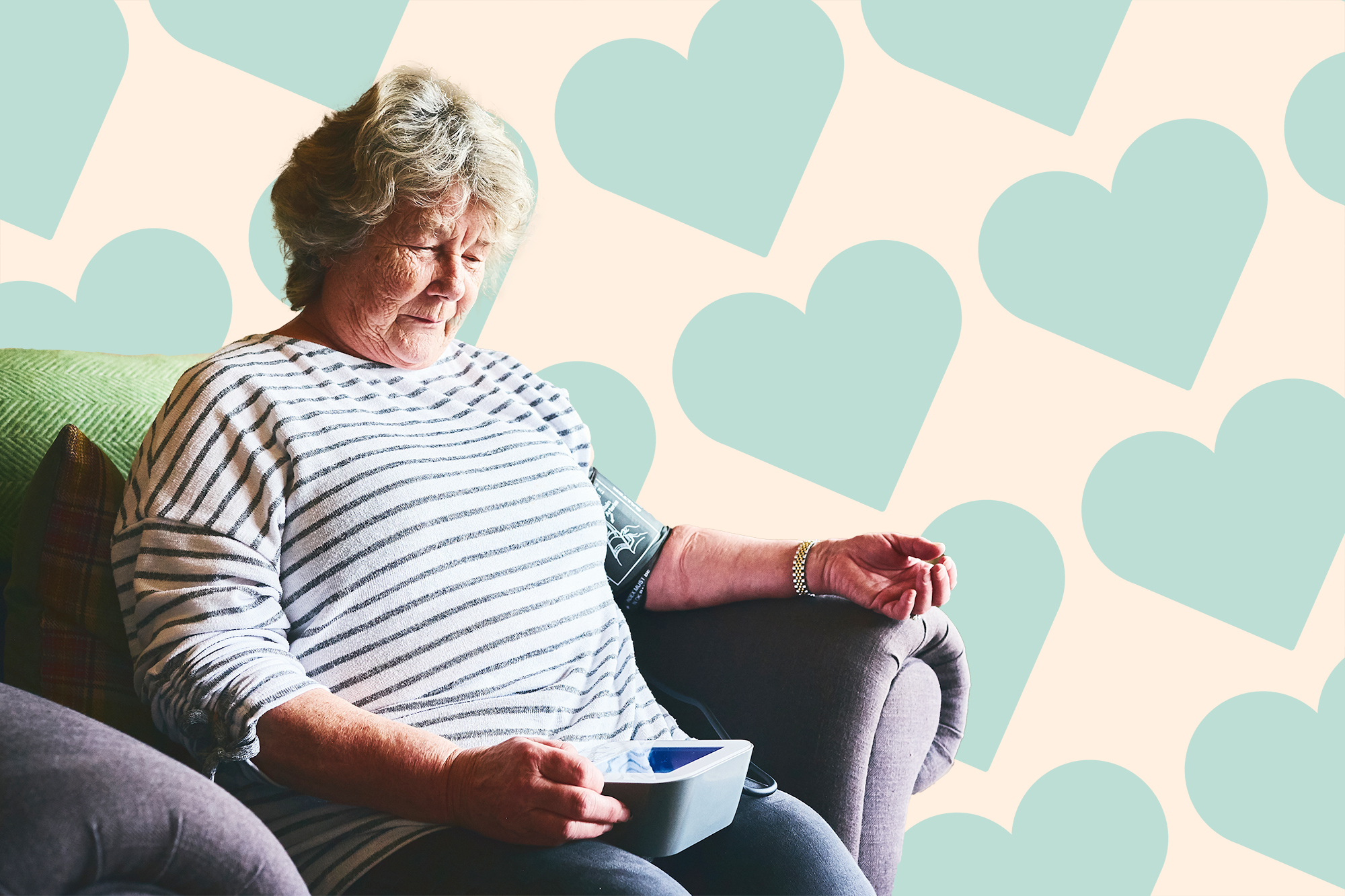 Senior woman measuring her blood pressure at home on a designed background