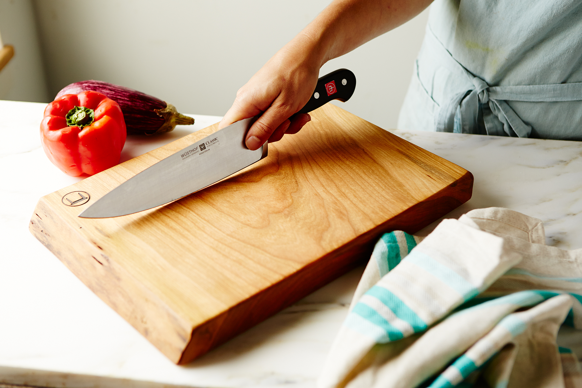 a woman's hand holding a kitchen knife