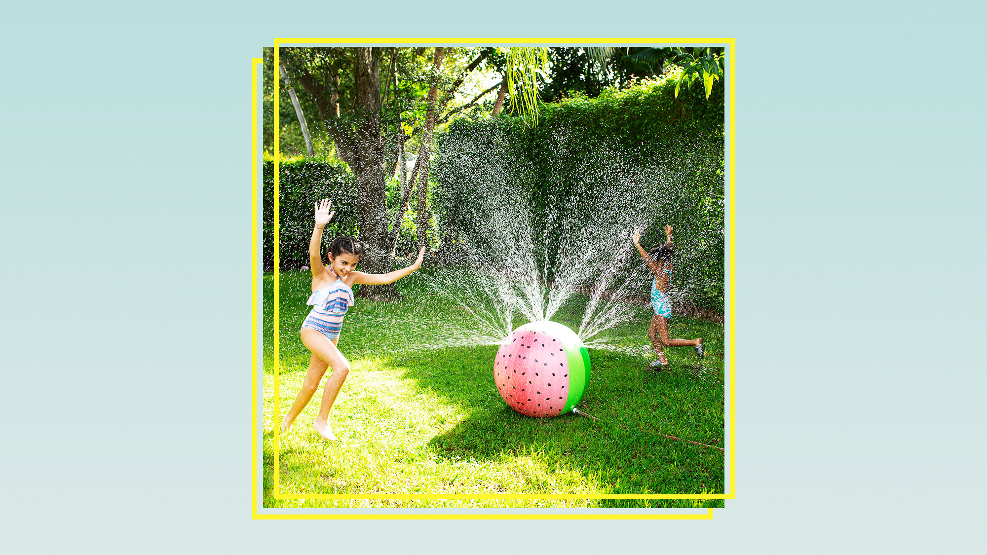 two kids playing in a sprinkler shaped like a watermelon