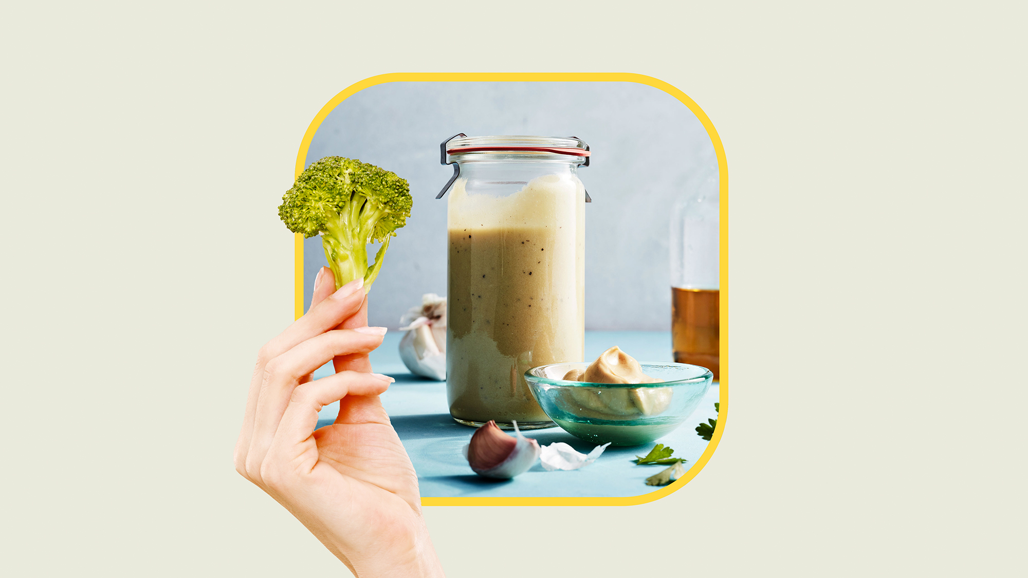 a picture of salad dressing with a yellow boarder with a hand holding broccoli in front of it