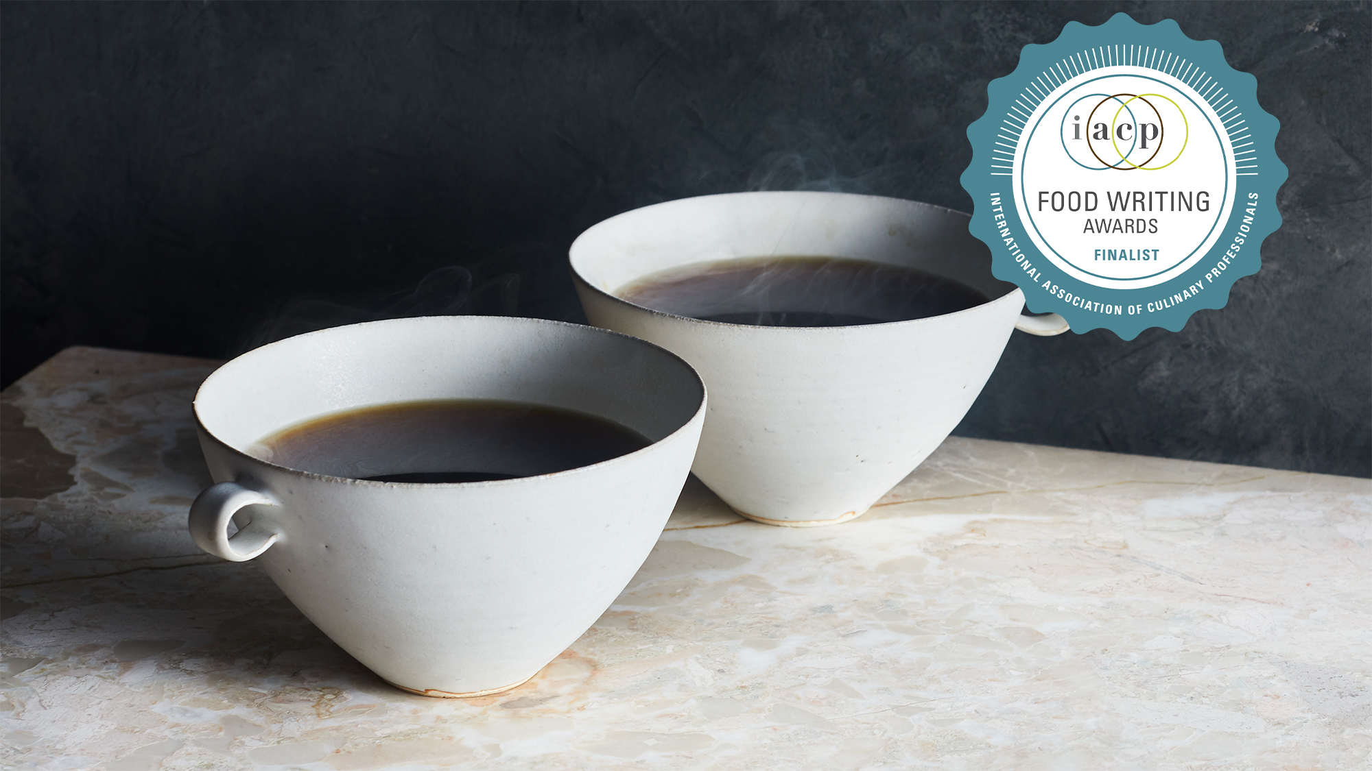 2 cups of coffee on a marble surface with a dark background