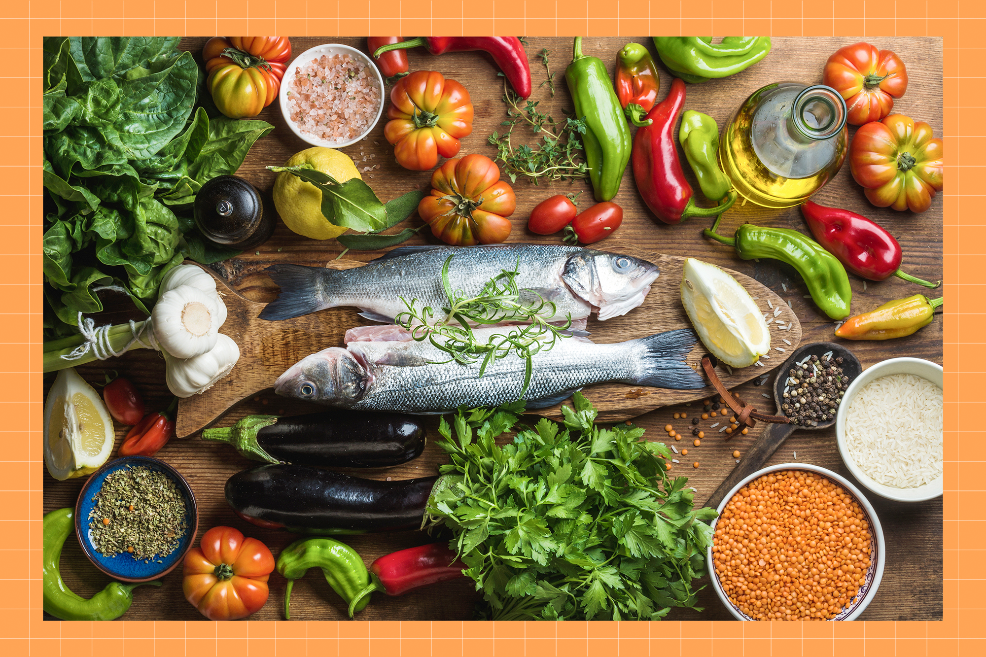Raw uncooked seabass fish with vegetables, grains, herbs and spices on chopping board over rustic wooden background with a photo treatment in the background