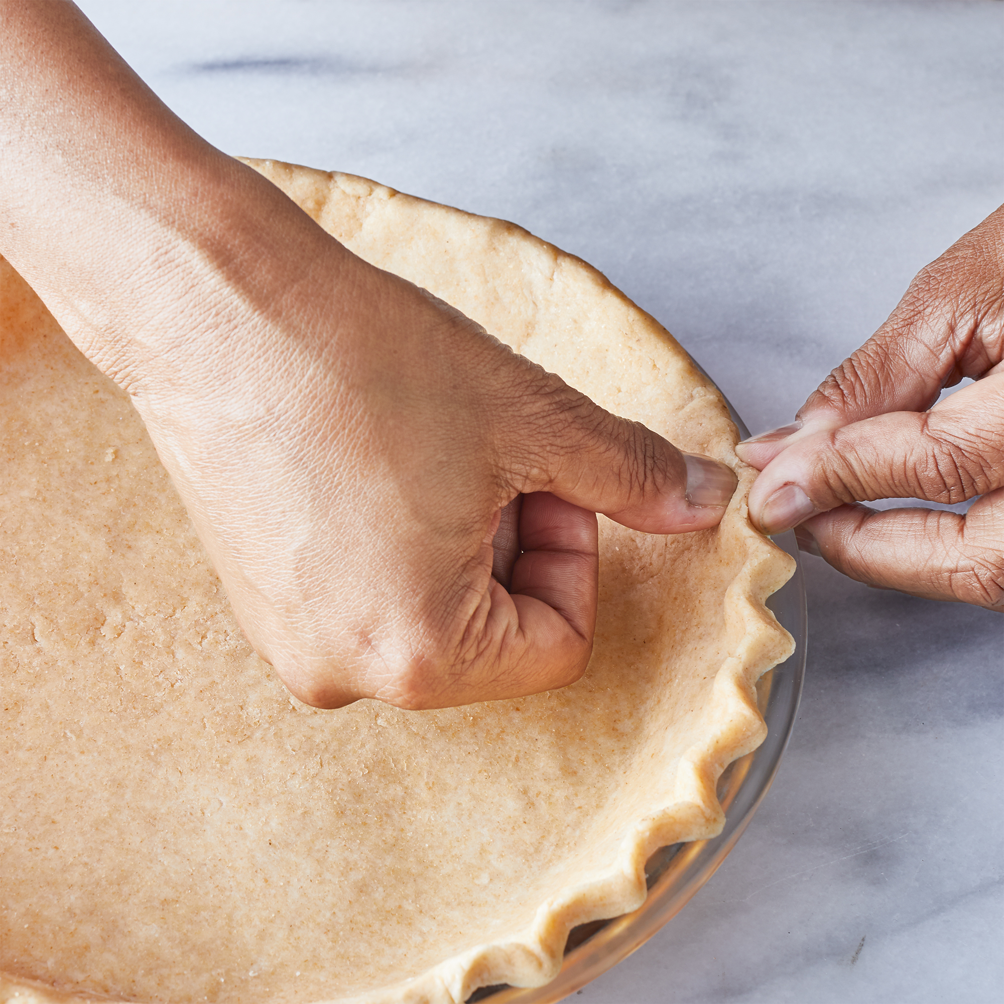 """two hands to pinching (""""flute"""") the edge of a pie crust"""