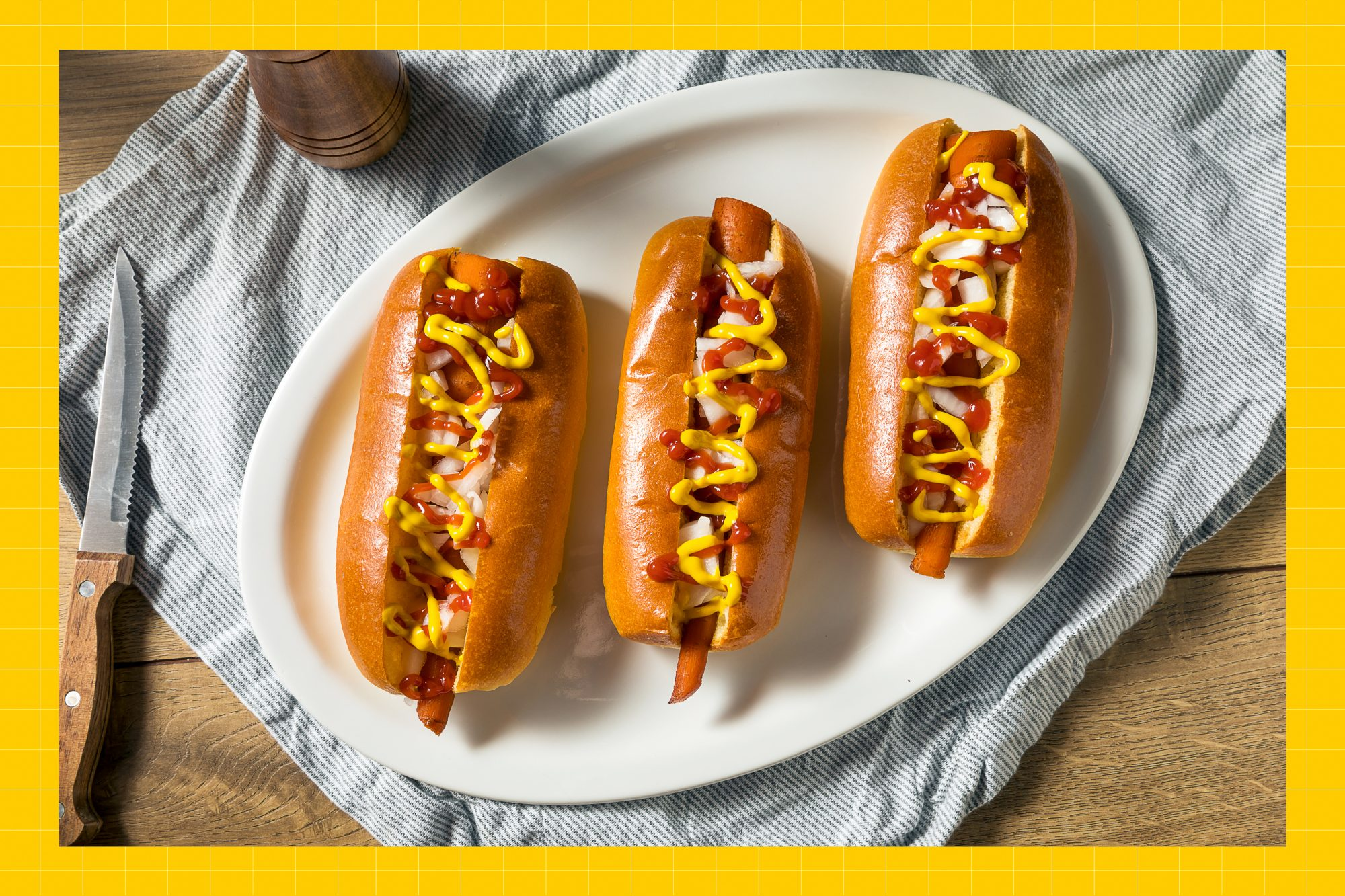 Carrot hotdogs in buns on a white plate with a blue and white dish towel and wood surface