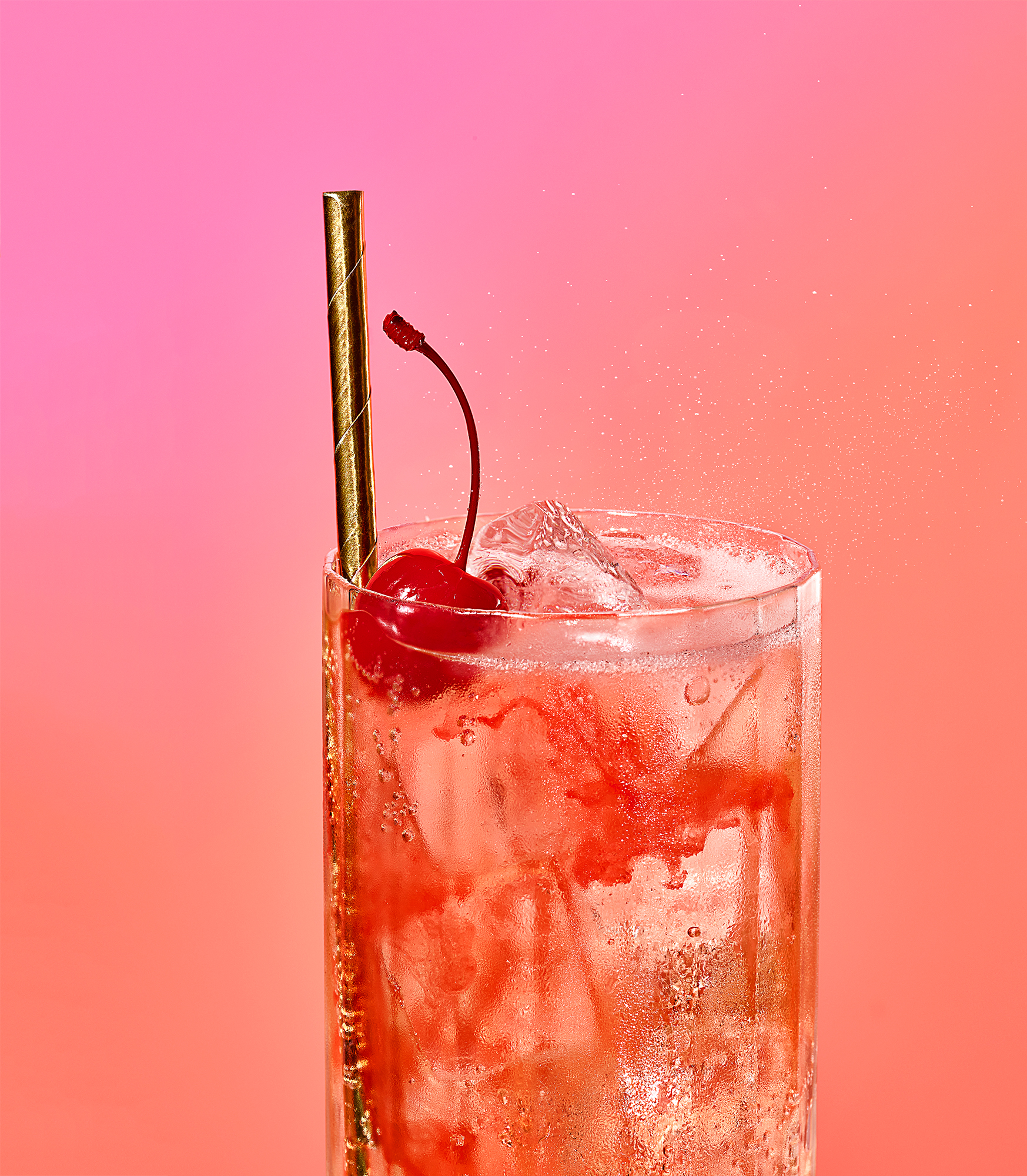 A soda in a glass with a cherry and straw on a bright pink background
