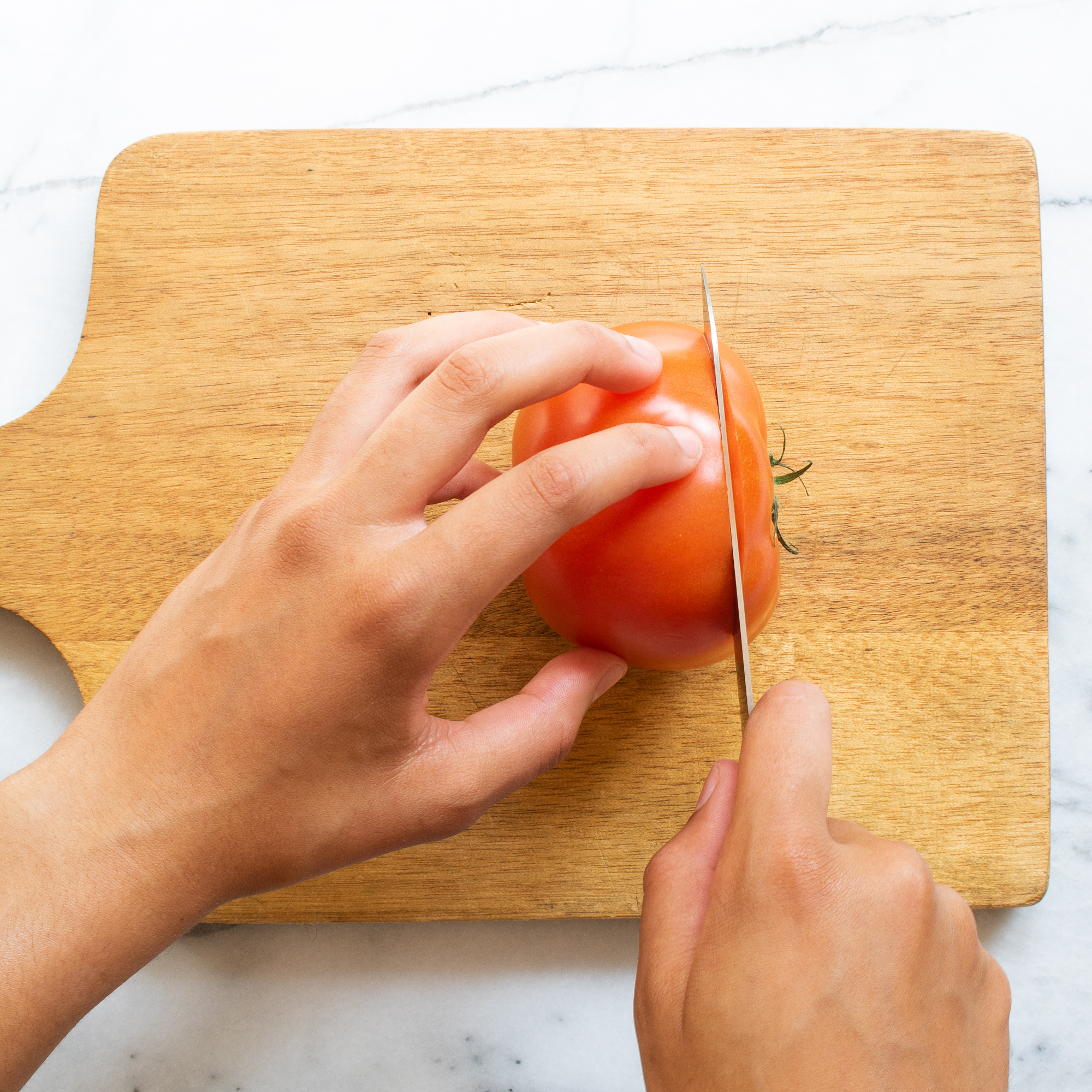 hands using a knife to slice tomatoes on a wood cutting board